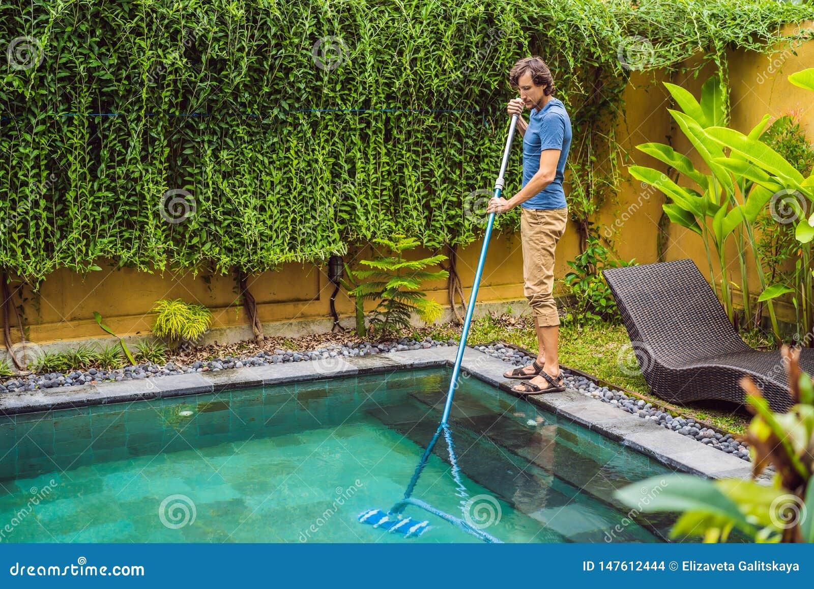 D?capant de la piscine Homme dans une chemise bleue avec l ?quipement de nettoyage pour des piscines Services de nettoyage de pis