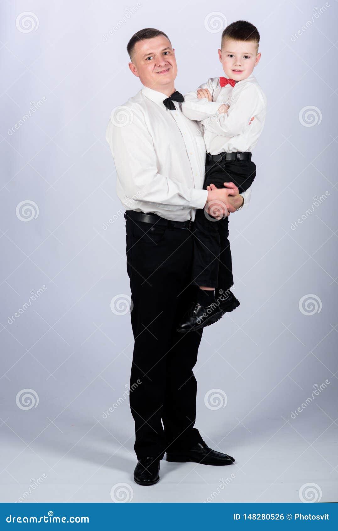 D?a de fiesta de la familia Relaciones del pap? y del hijo r El padre lleva el equipo formal de la ropa del hijo del abrazo Crezc