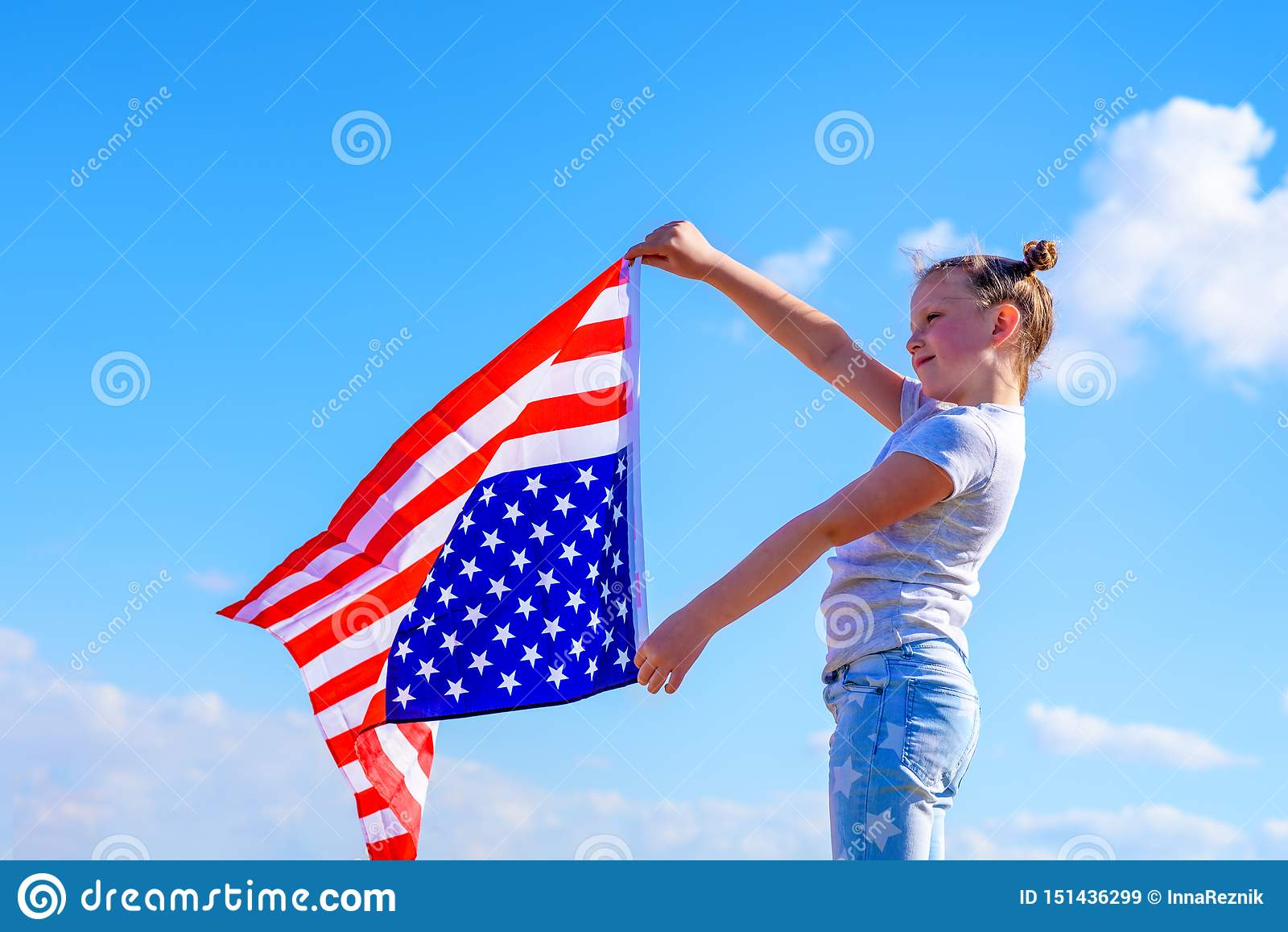 D?a de fiesta patri?tico Ni?o feliz, muchacha linda del peque?o ni?o con la bandera americana Los E.E.U.U. celebran el 4 de julio