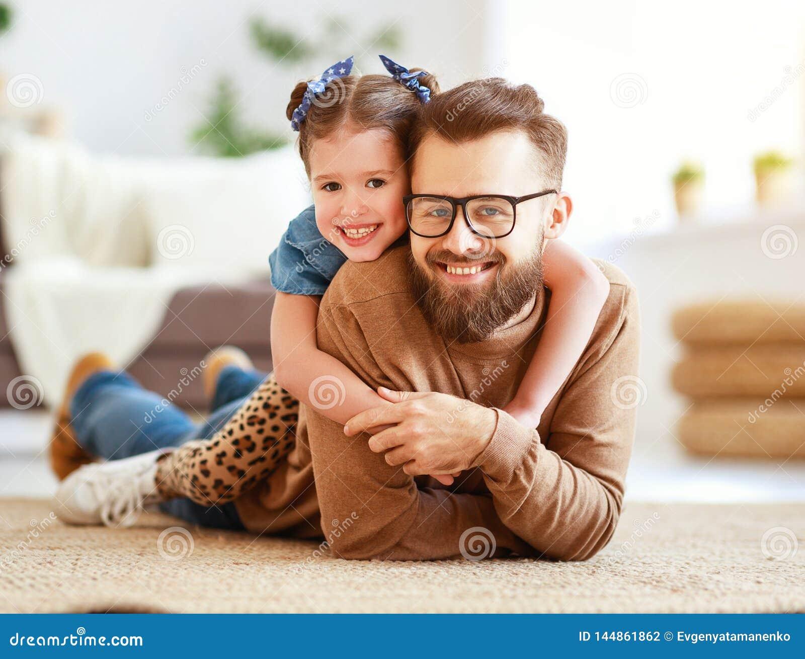 D?a del `s del padre La hija feliz de la familia abraza a su pap?