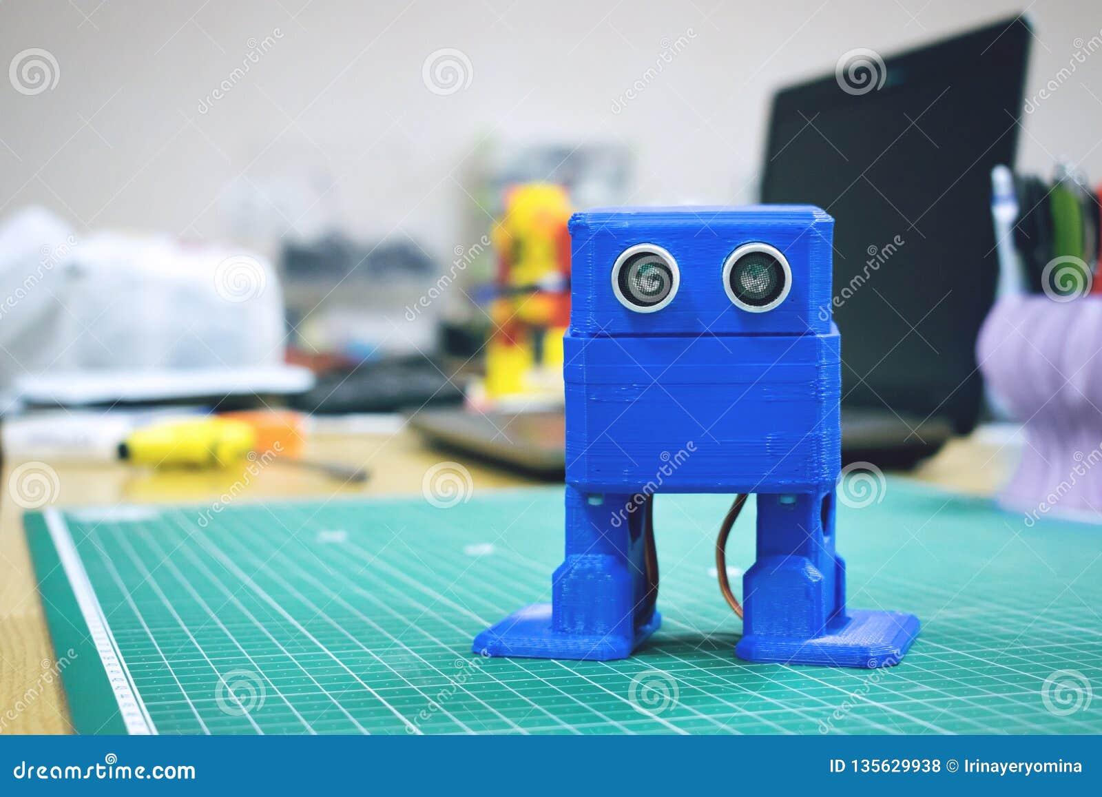 3D gedrukte Grappige dansende blauwe robot op de achtergrond van apparaten en laptop Robotmodel op automatische driedimensionele