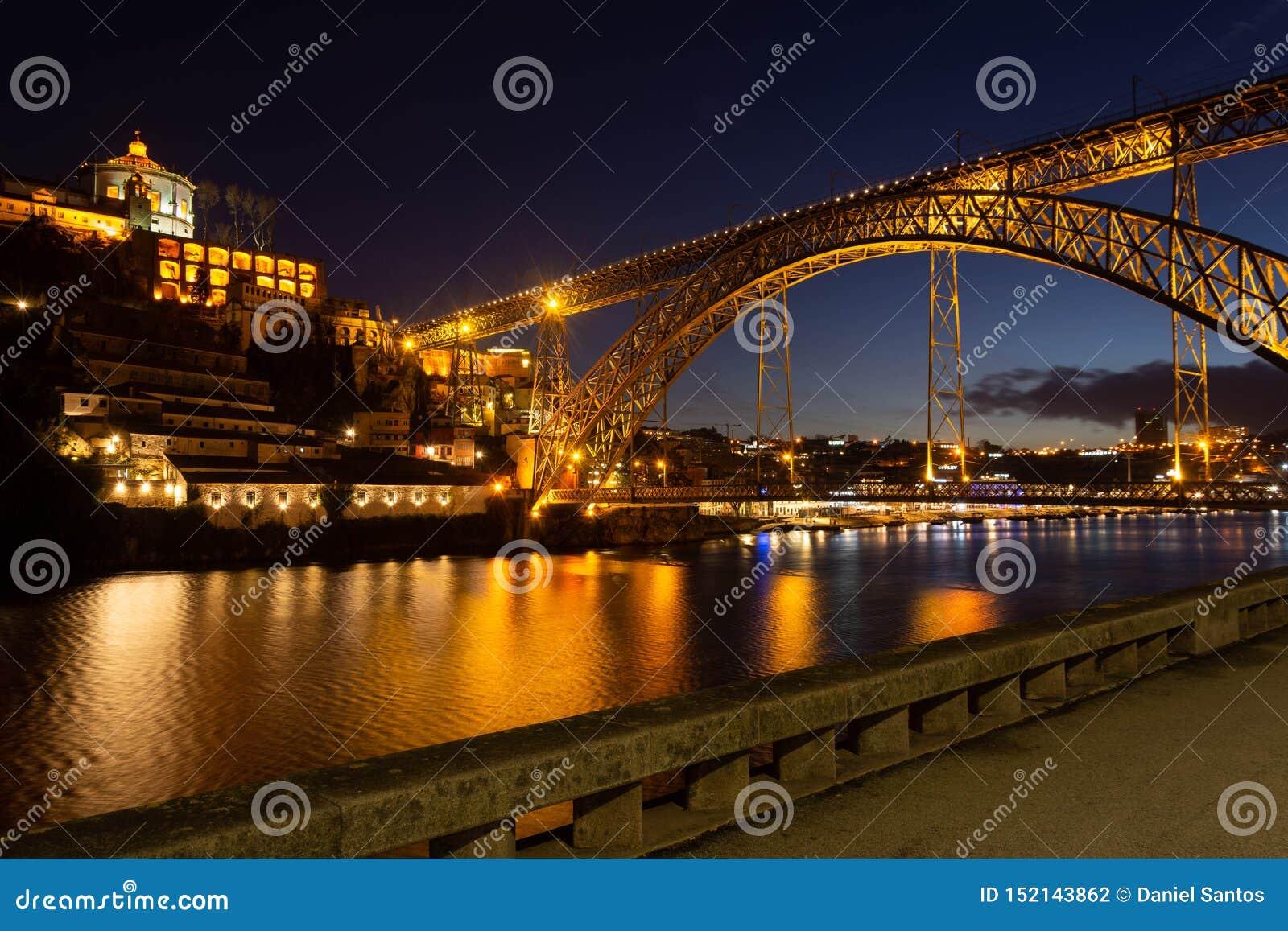 D Luis I brug bij nacht wordt verlicht die De rivier van Douro Porto stad