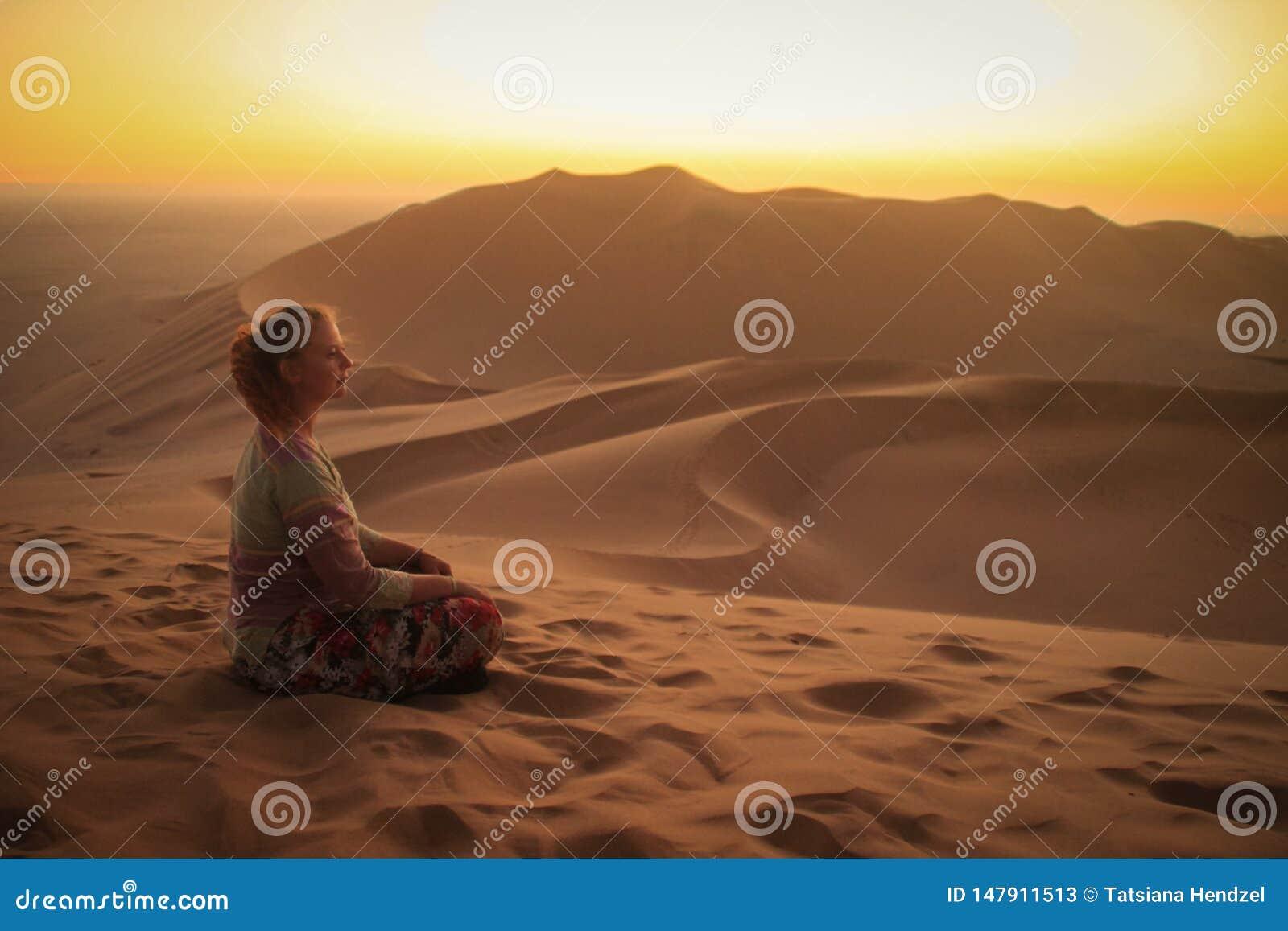 D?sert de Namib, en parc national de Namib-Nacluft en Namibie Sossusvlei Touriste de jeune femme faisant le yoga et la relaxation