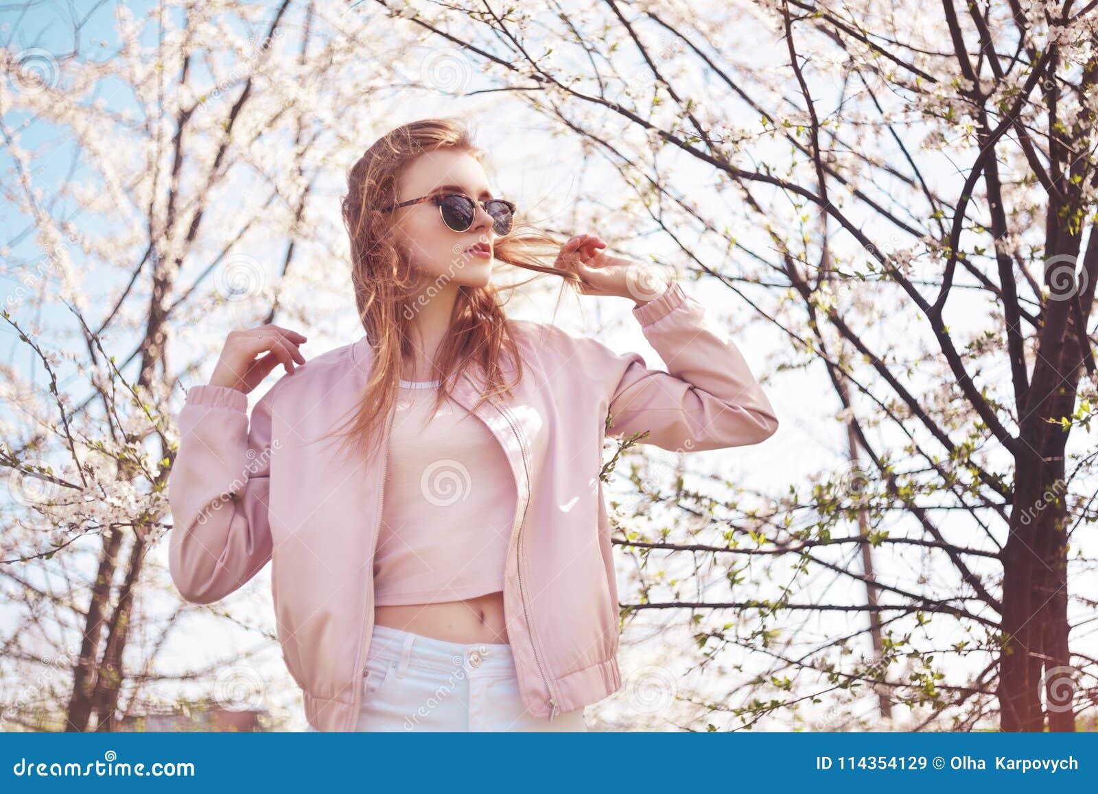 Da mola da forma da menina retrato fora em árvores de florescência Mulher romântica da beleza nas flores nos óculos de sol Senhor