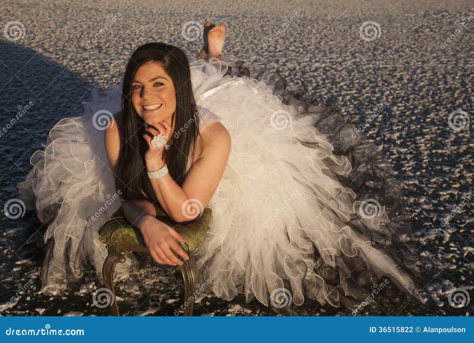 Da mulher do vestido formal do gelo sorriso da configuração com os pés descalços