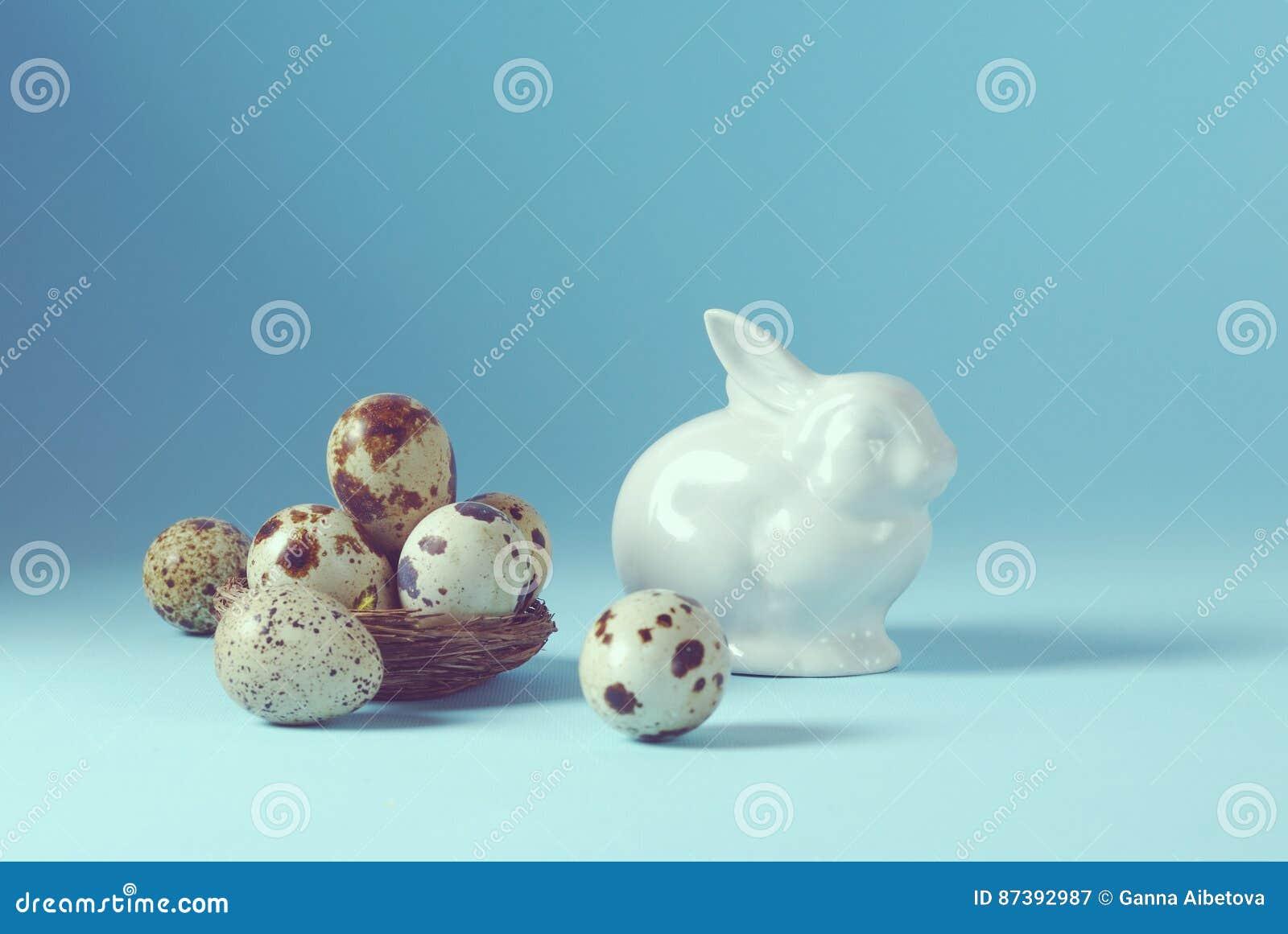 Da Páscoa do feriado fundo da vida ainda com os ovos brancos do coelho e de codorniz da porcelana no vintage decorativo do ninho