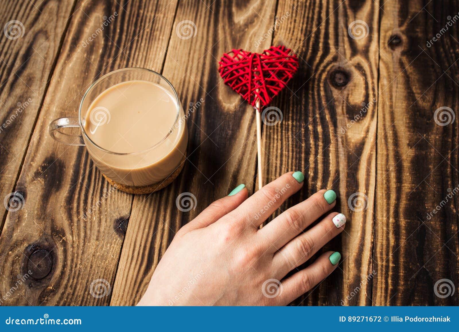 Da xícara de café brilhante do tratamento de mãos da mão da mulher coração feito a