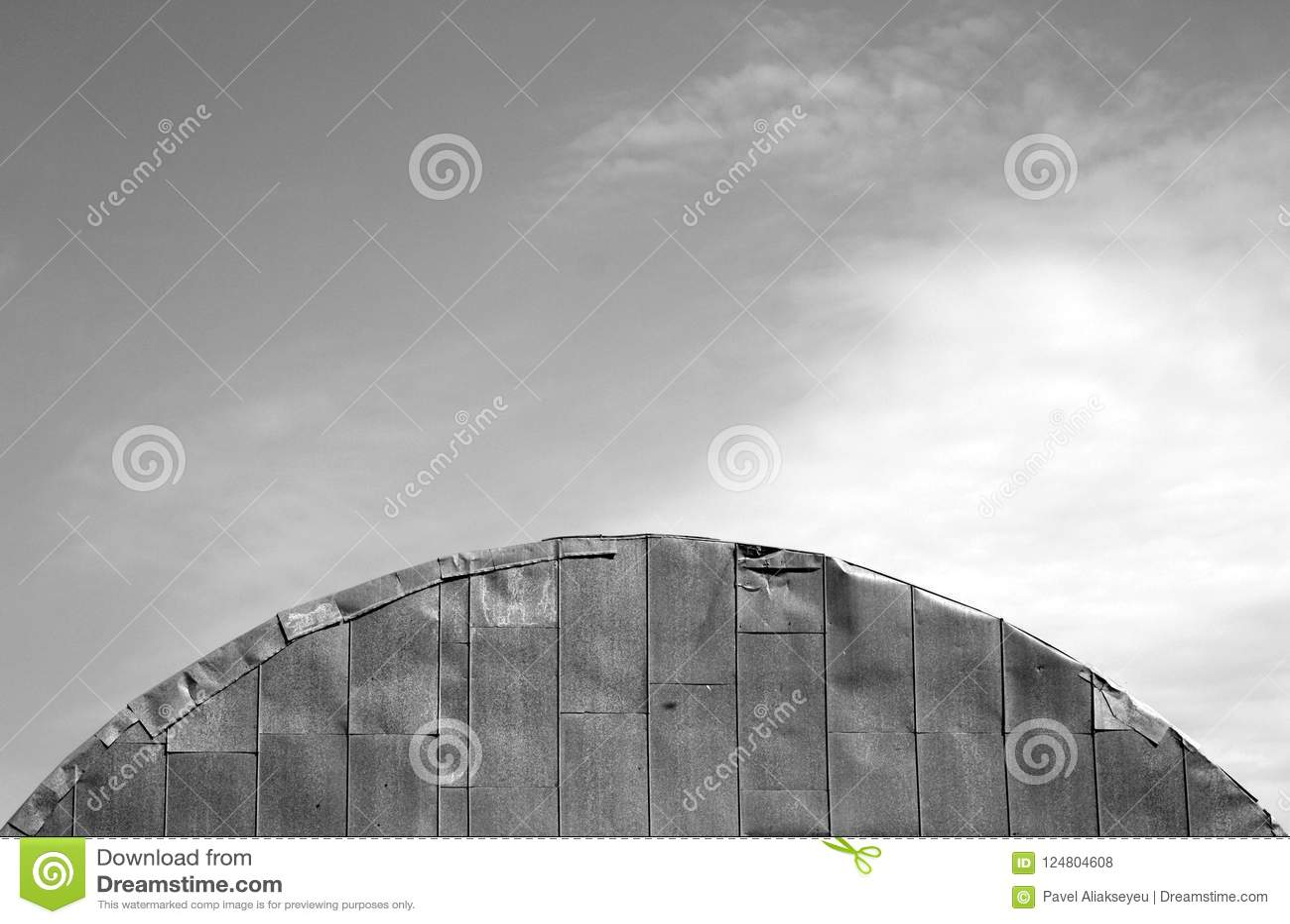 Dach stary metalu hangar przeciw chmurnemu niebu w czarny i biały