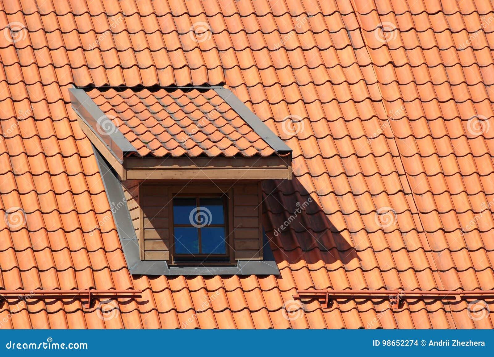 dachbodenfenster im orange mit ziegeln gedeckten dach stockfoto
