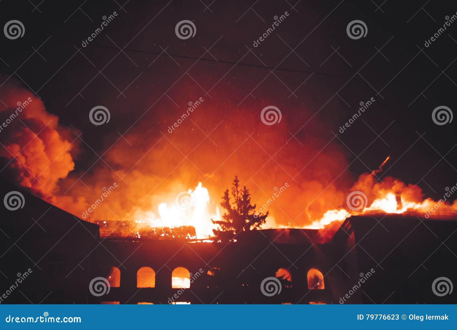 Dachowy budynek Na ogieniu Przy nocą