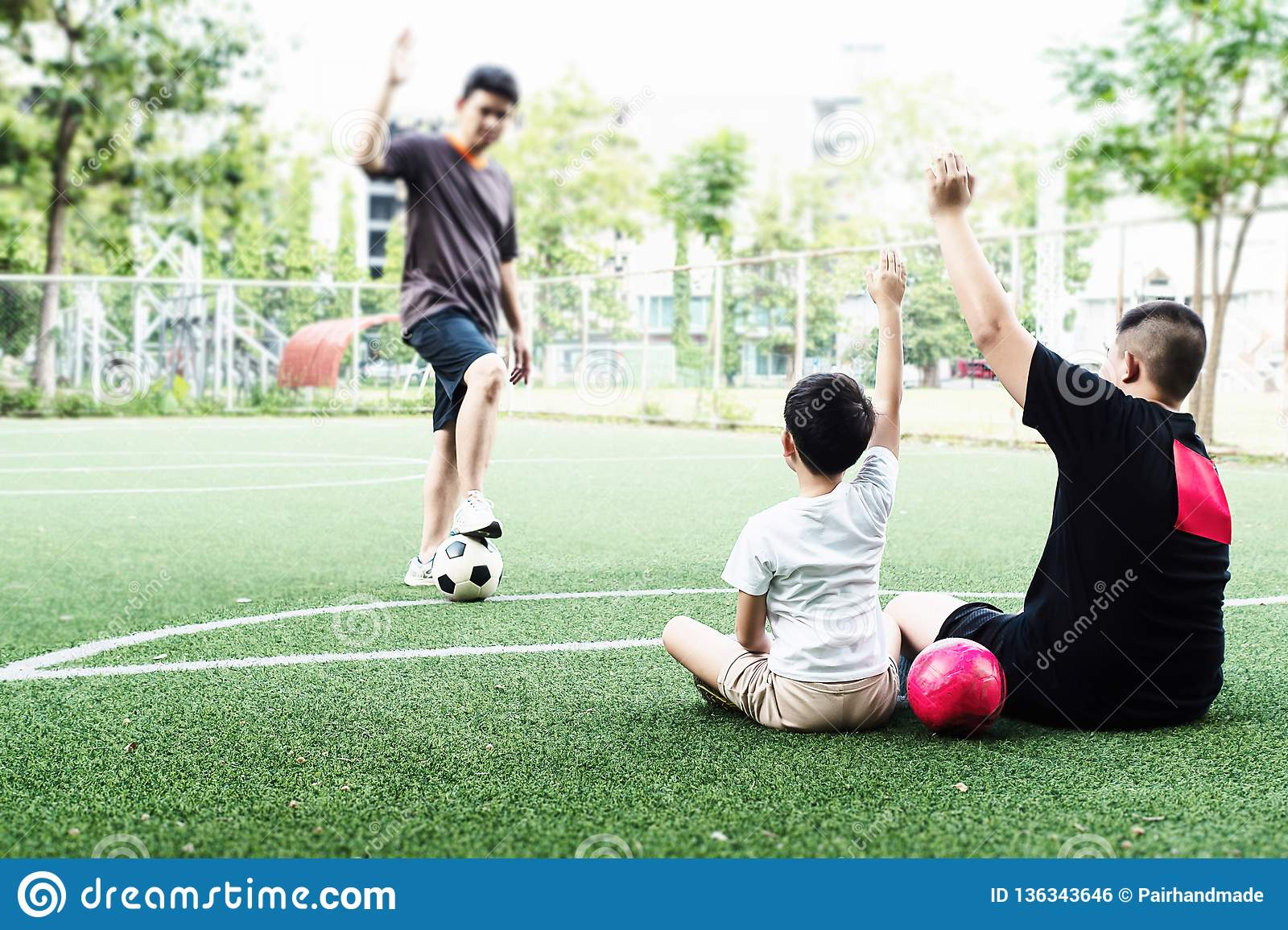 Dad coaches his children how to play soccer
