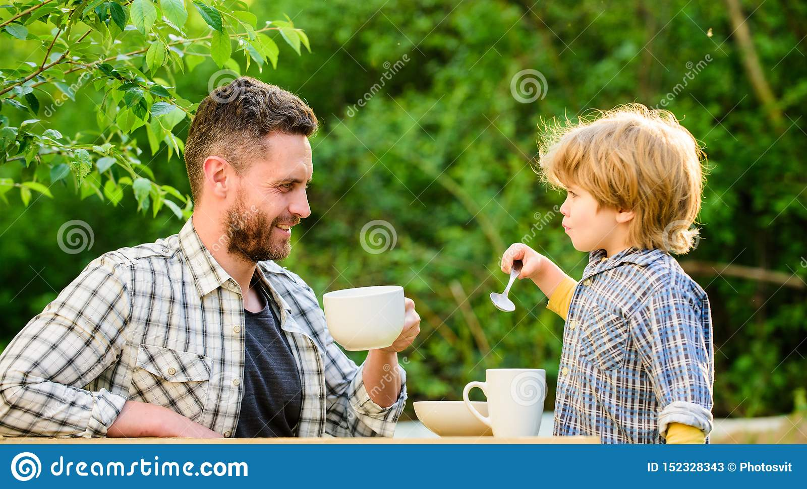 Dad and cute toddler boy having lunch outdoors. Child care. Feeding son natural foods. Feed in right way for childs