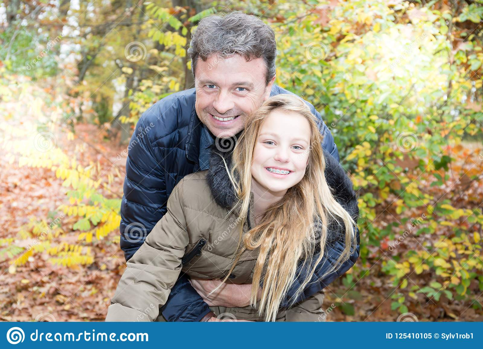 Father and daughter in the autumn park play laughing pretty blonde girl hugs her dad