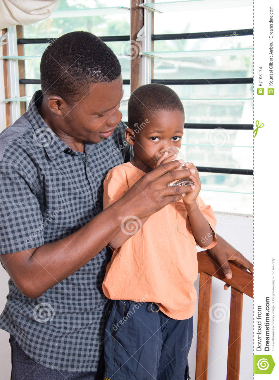 Dad gives water to drink to his child