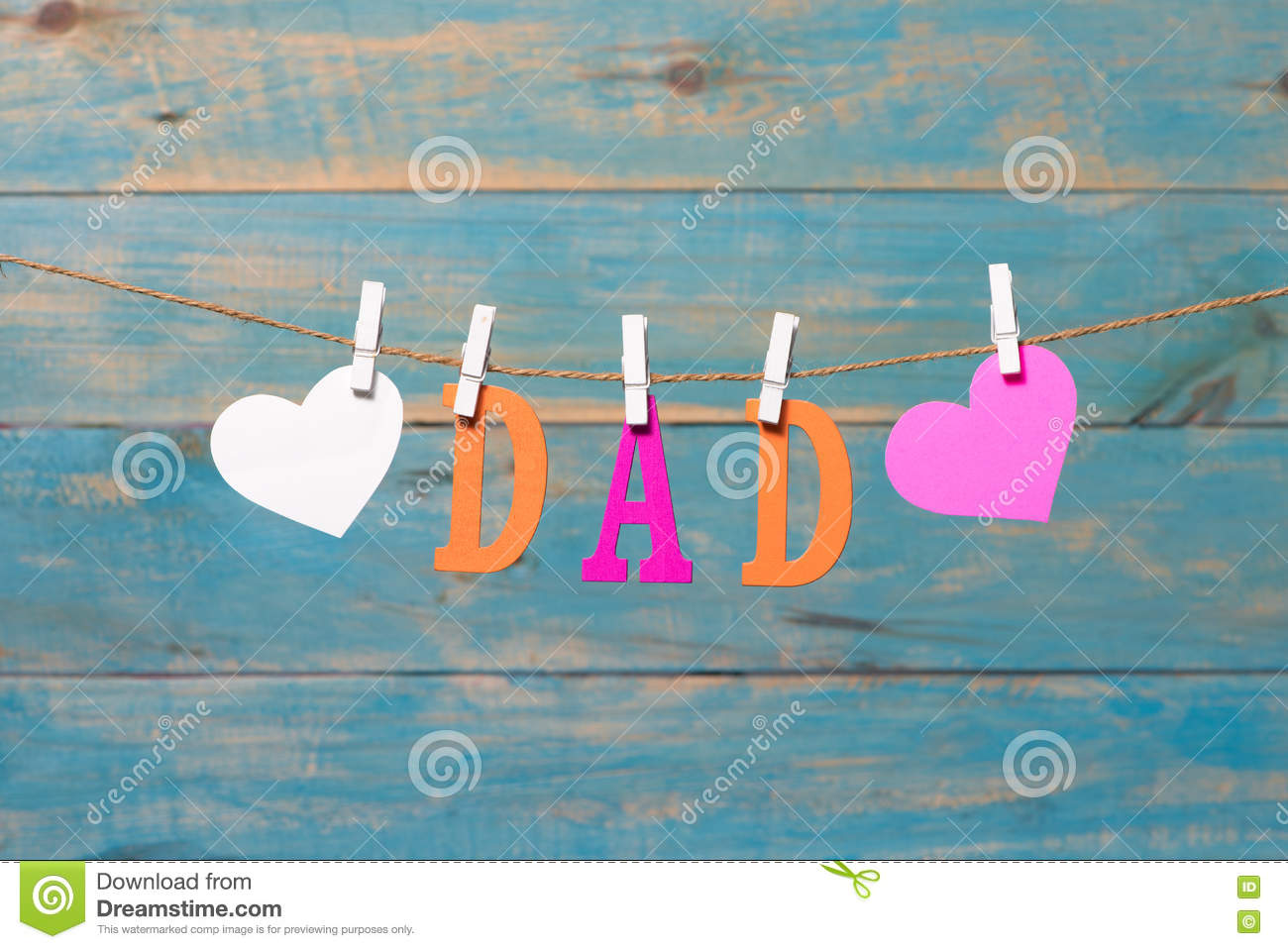 dad letters fathers day message with hearts hanging with clothespins over blue wooden board