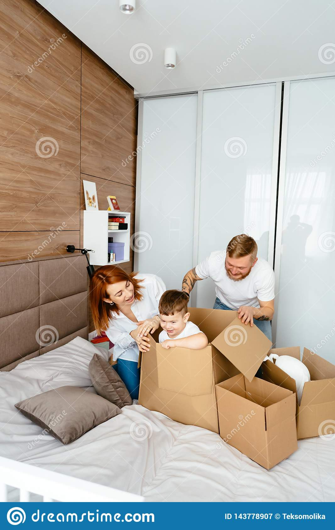 Dad mom and little son play in the bedroom with paper boxes
