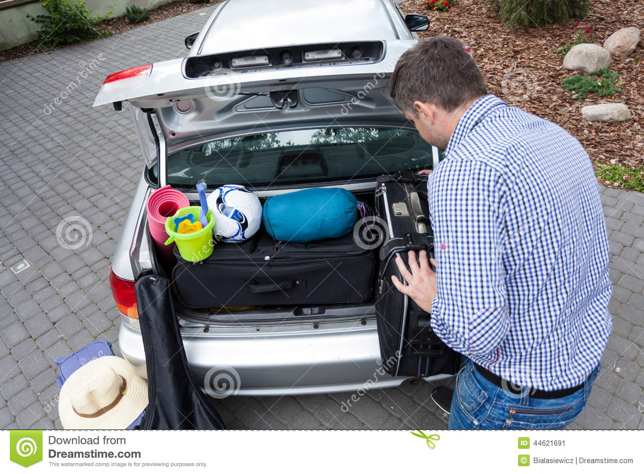 Dad Preparing Car Trunk For Holiday Stock Photo