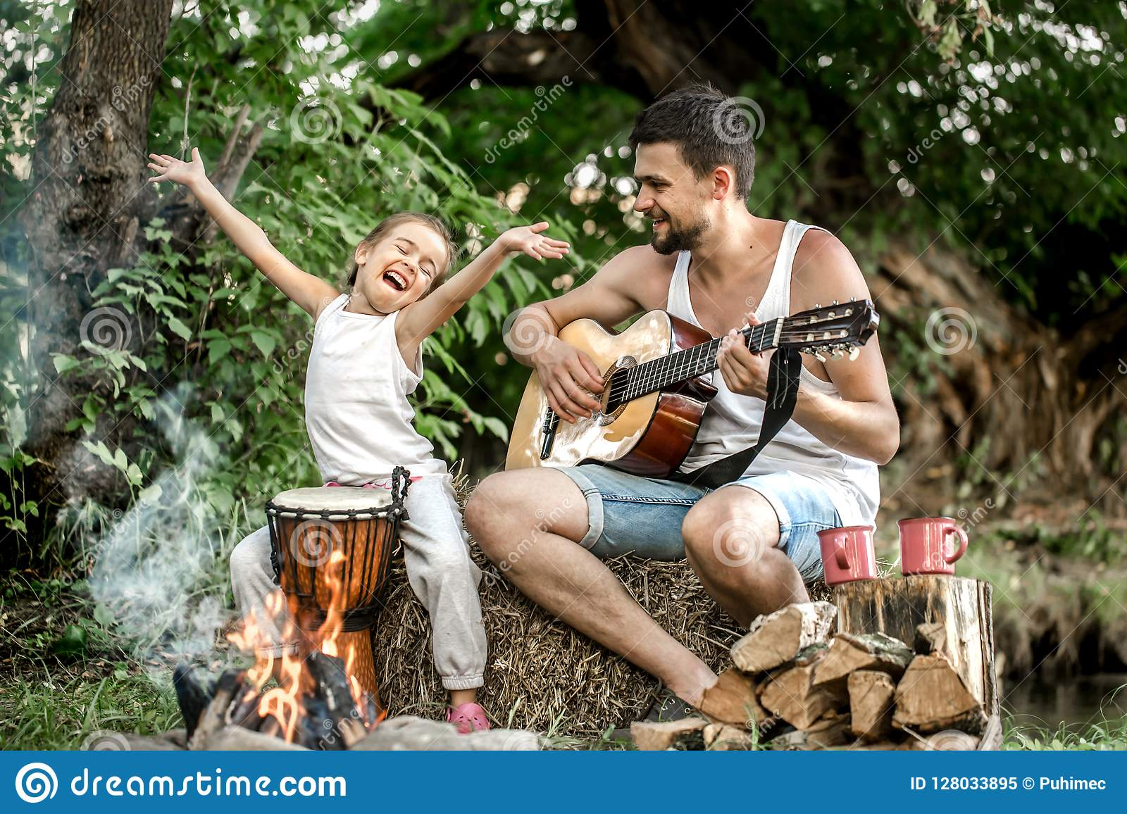 Dad plays the guitar, daughter on the nature