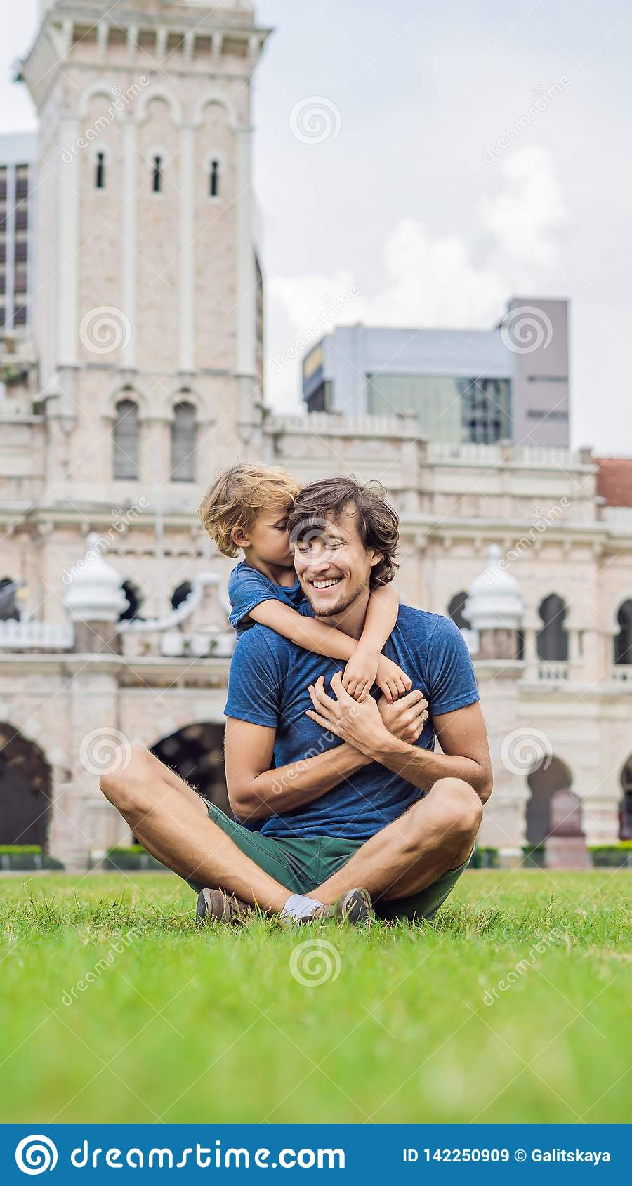 Dad and son on background of Merdeka square and Sultan Abdul Samad Building. Traveling with children concept VERTICAL