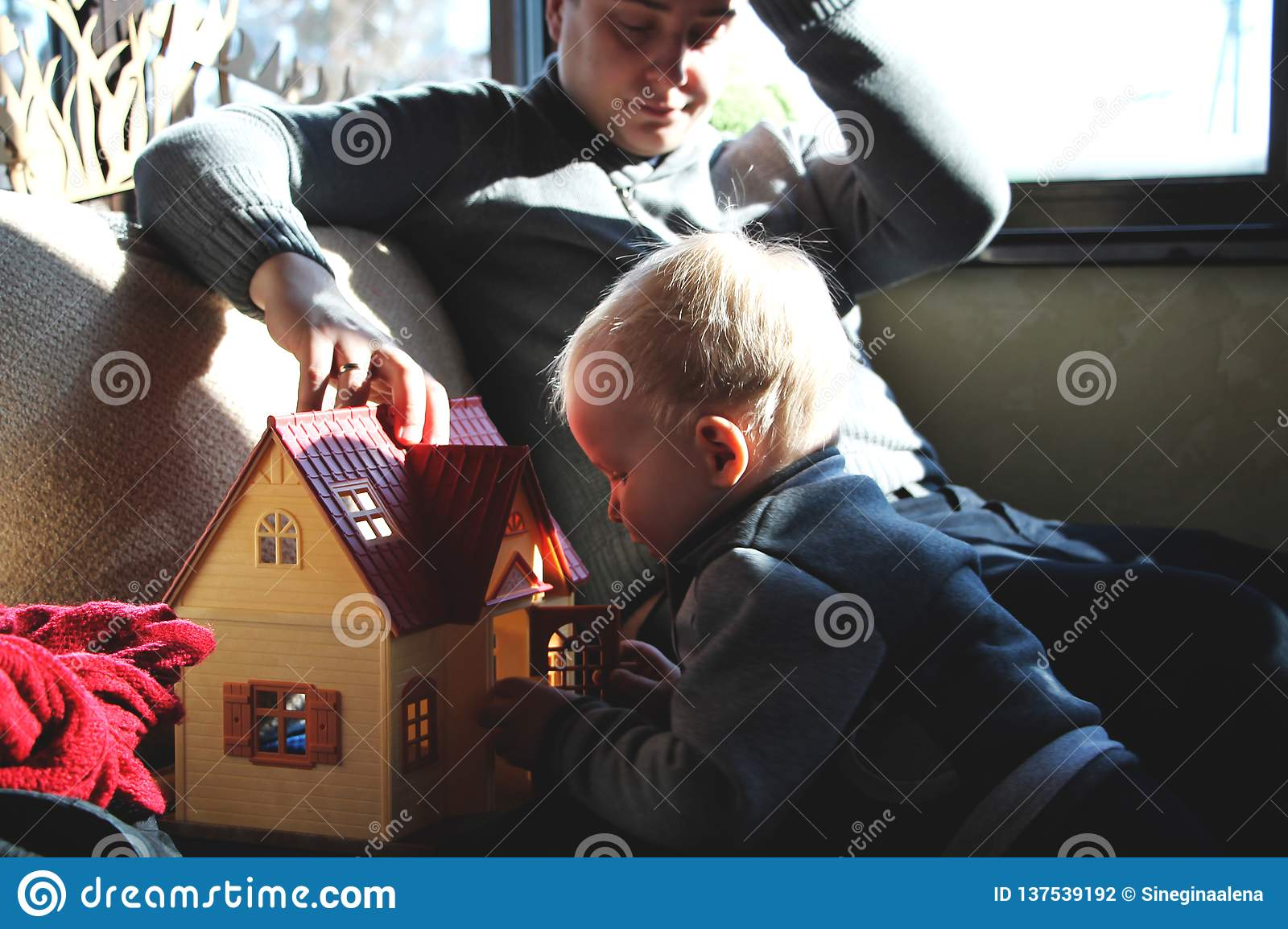 Dad and son are playing in the doll house