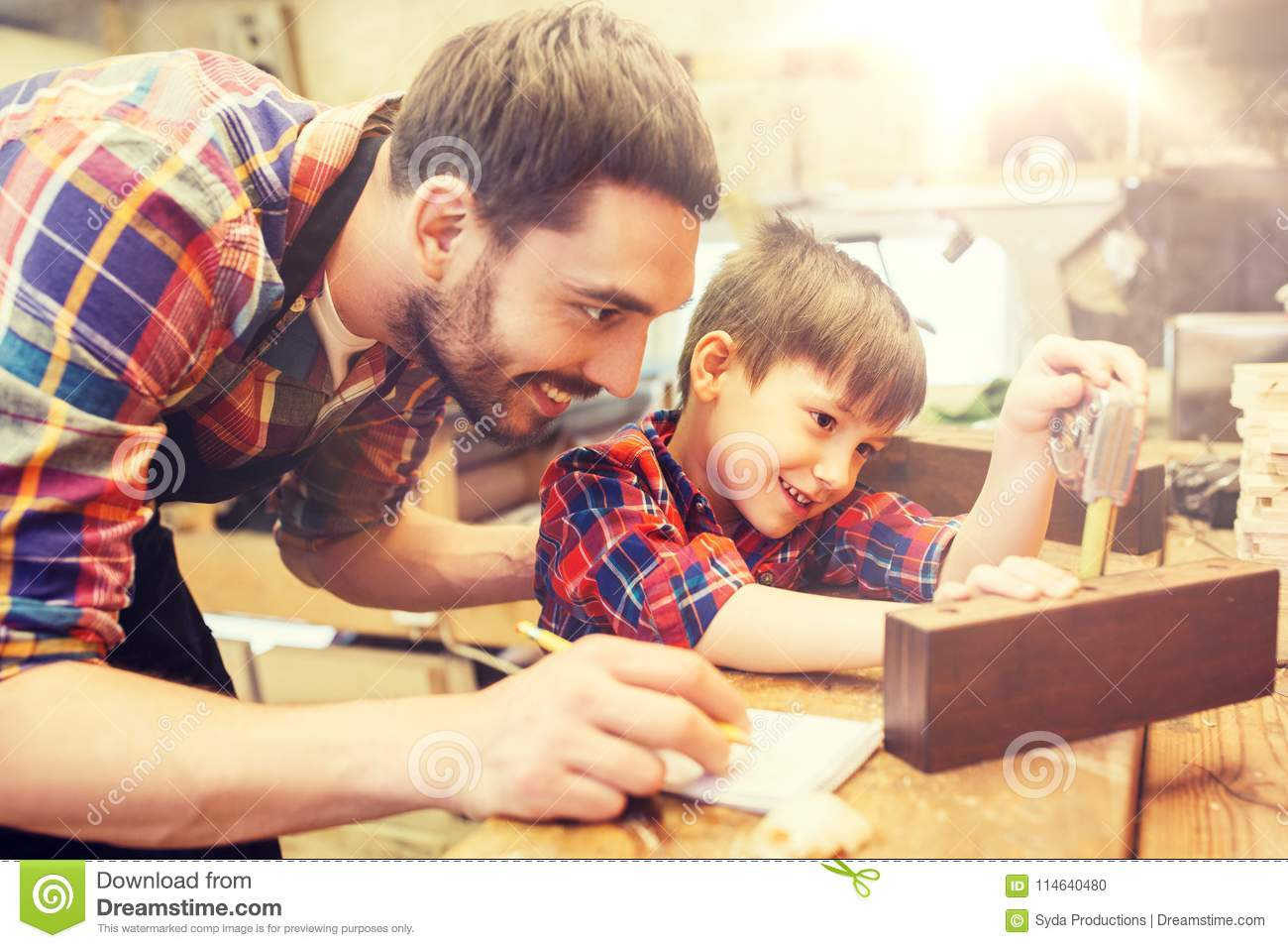 Dad and son with ruler measuring plank at workshop