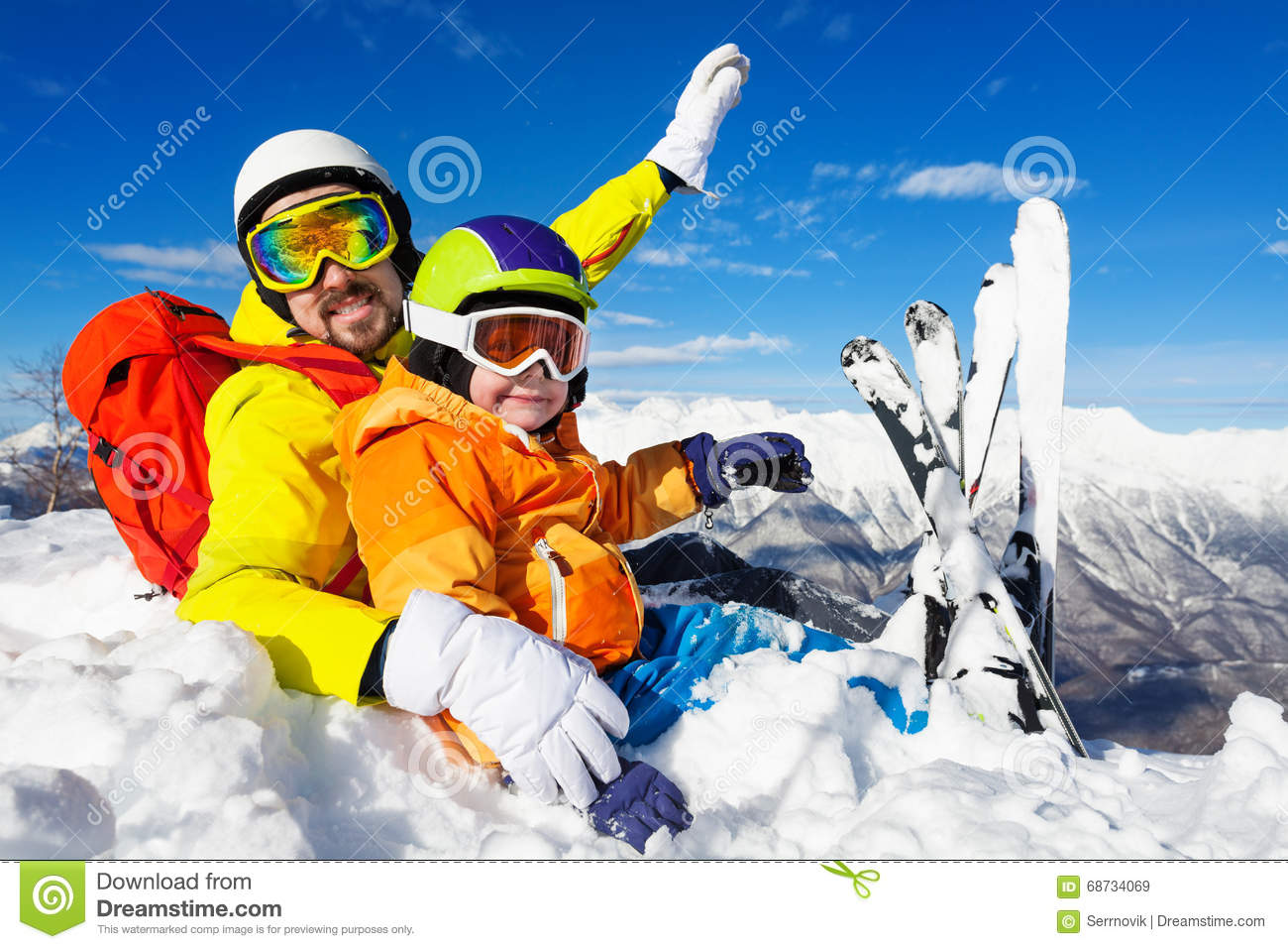 Dad And Son Skiers Sit In Snow On Mountain Top Stock Image