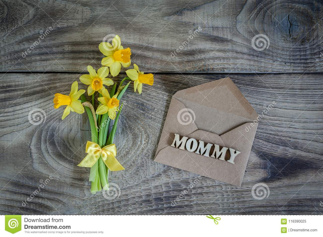 Daffodils with envelope on wooden background. Greeting card.