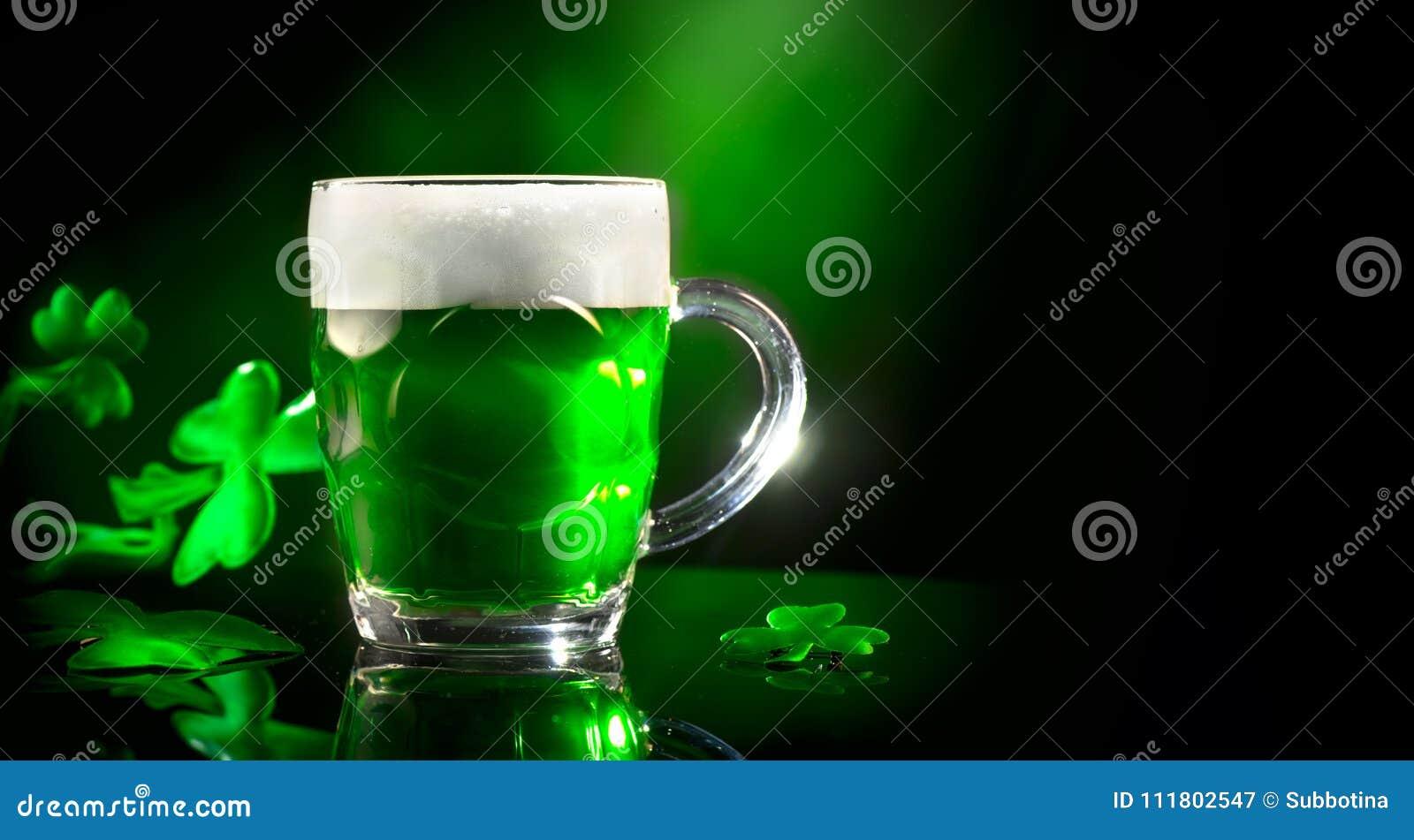 Dag för St Patrick ` s Grön halv liter för öl över mörker - grön bakgrund som dekoreras med treklöversidor