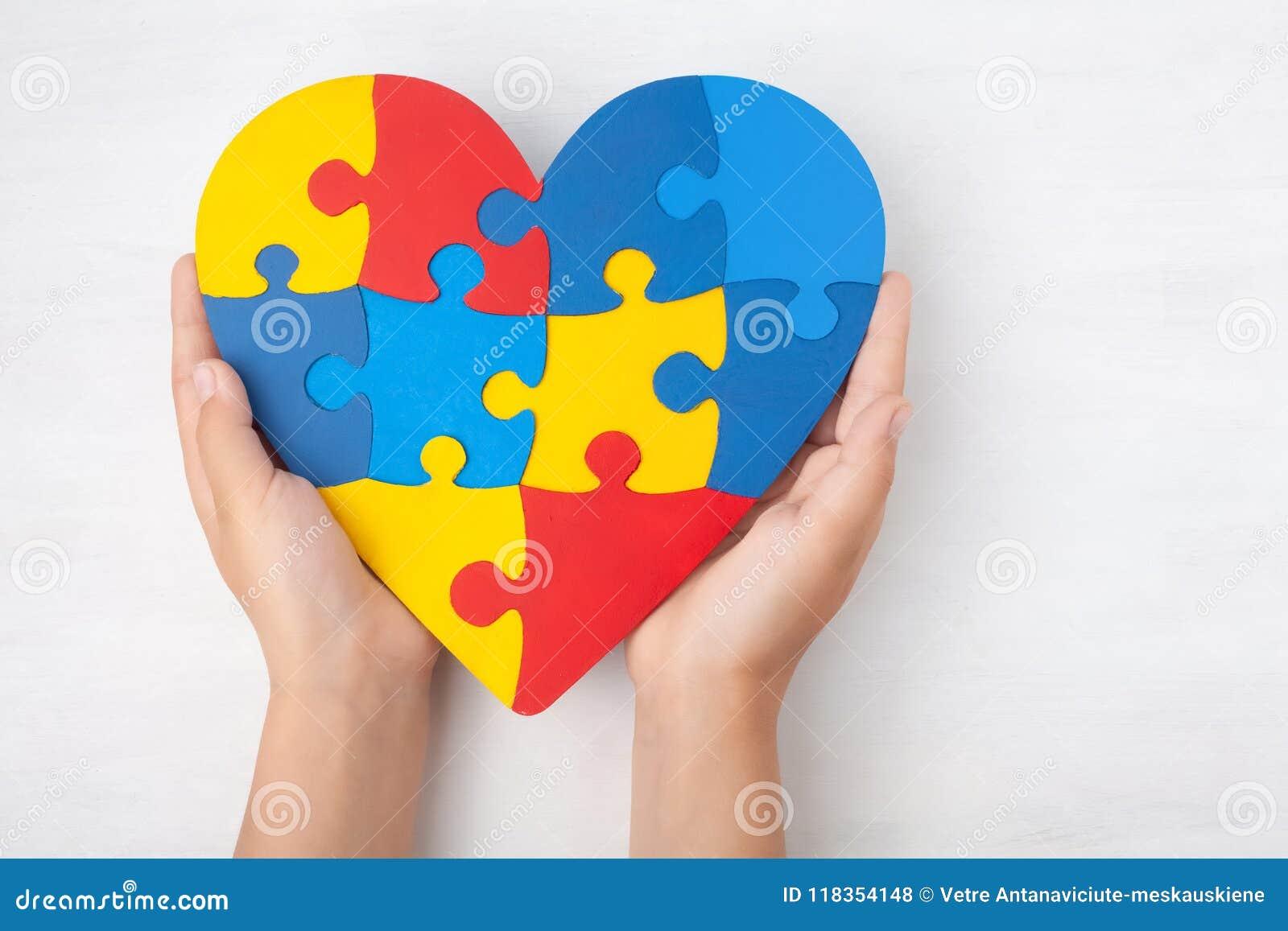 Dag för världsautismmedvetenhet, mentalt hälsovårdbegrepp med pusslet eller figursågmodell på hjärta med händer för barn` s
