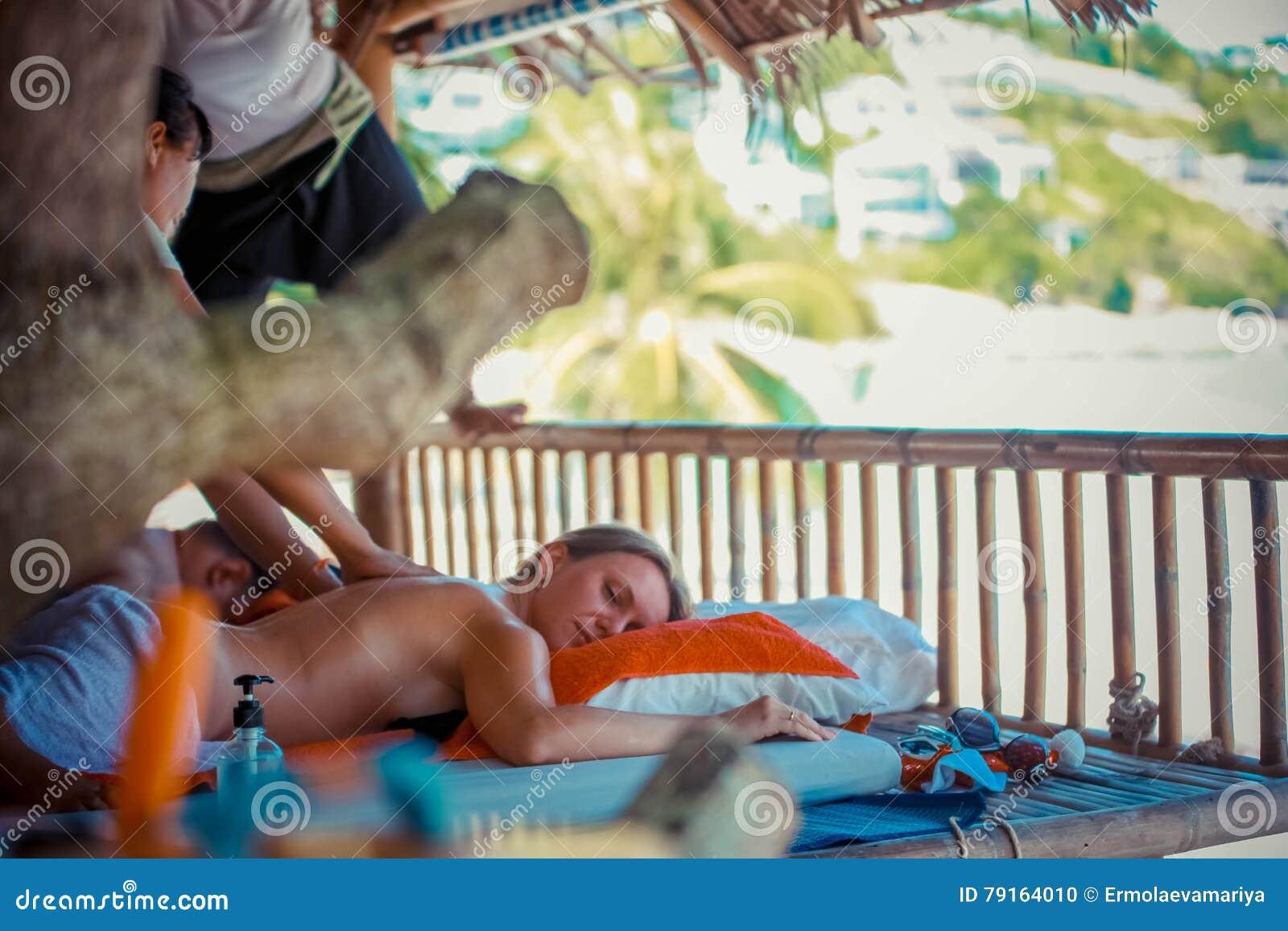 Dag i strandbrunnsort Thailändsk kvinna som gör massage