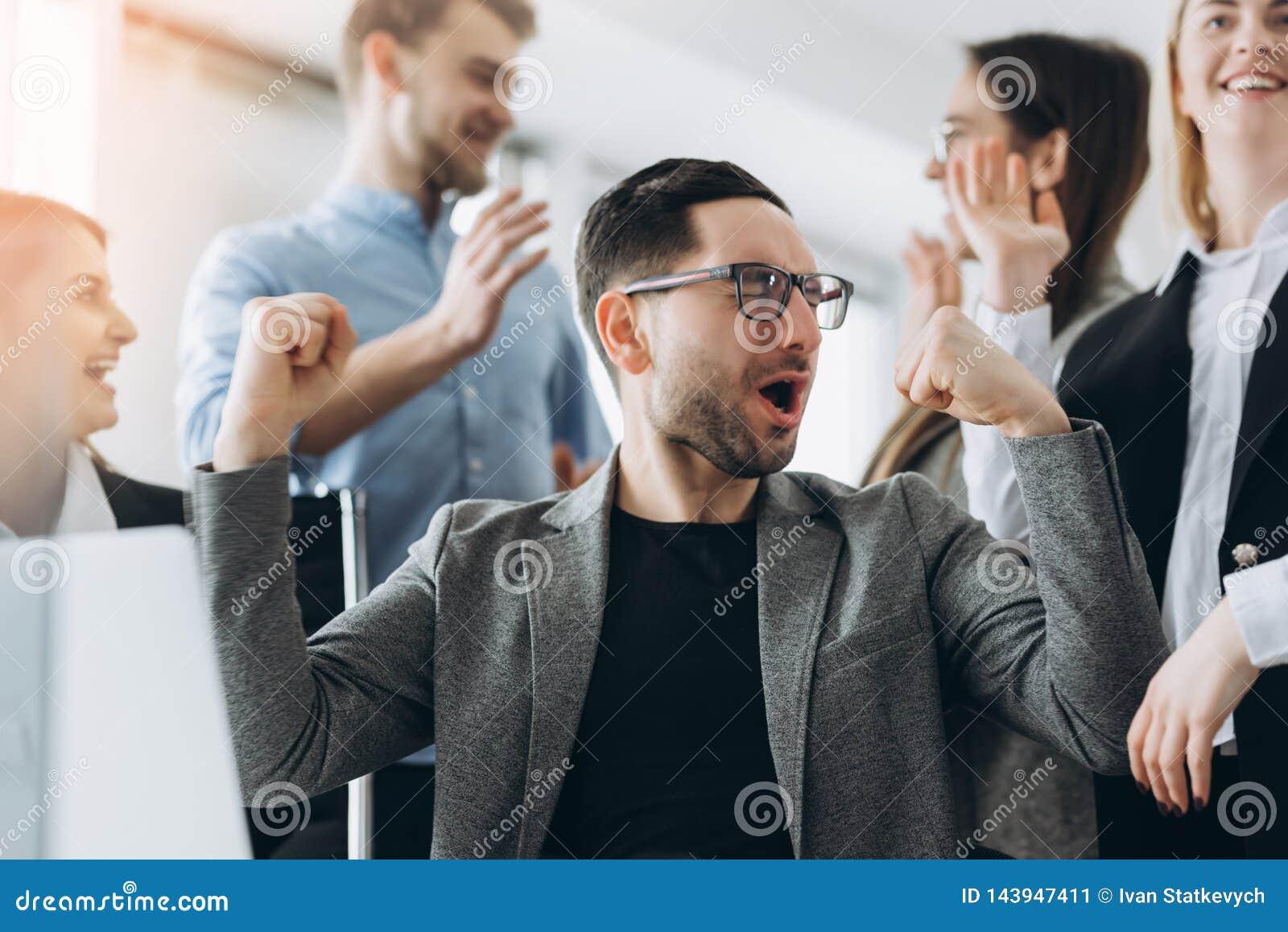 Dagelijkse winnaars Groep gelukkige bedrijfsmensen die in slimme vrijetijdskleding laptop en het gesturing bekijken Het bereiken