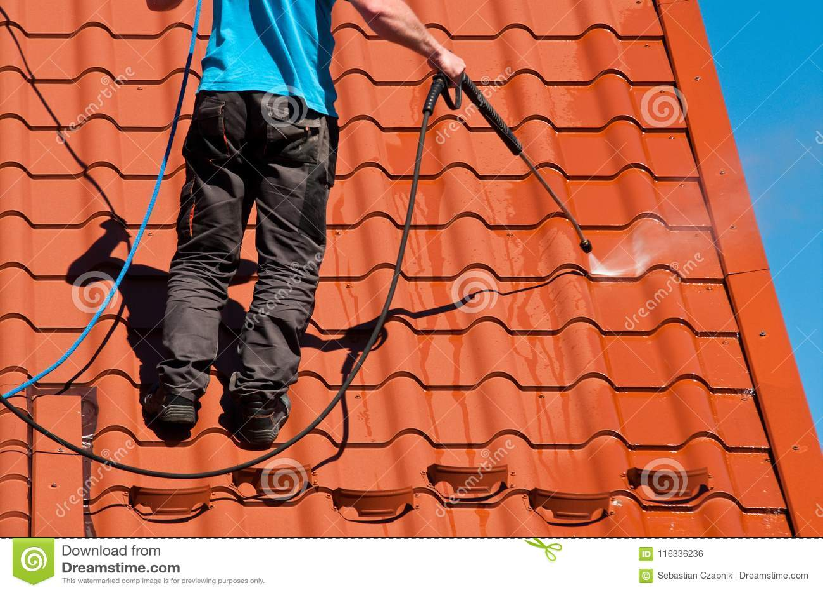Dak van het arbeiders het schoonmakende metaal met hoge drukwater