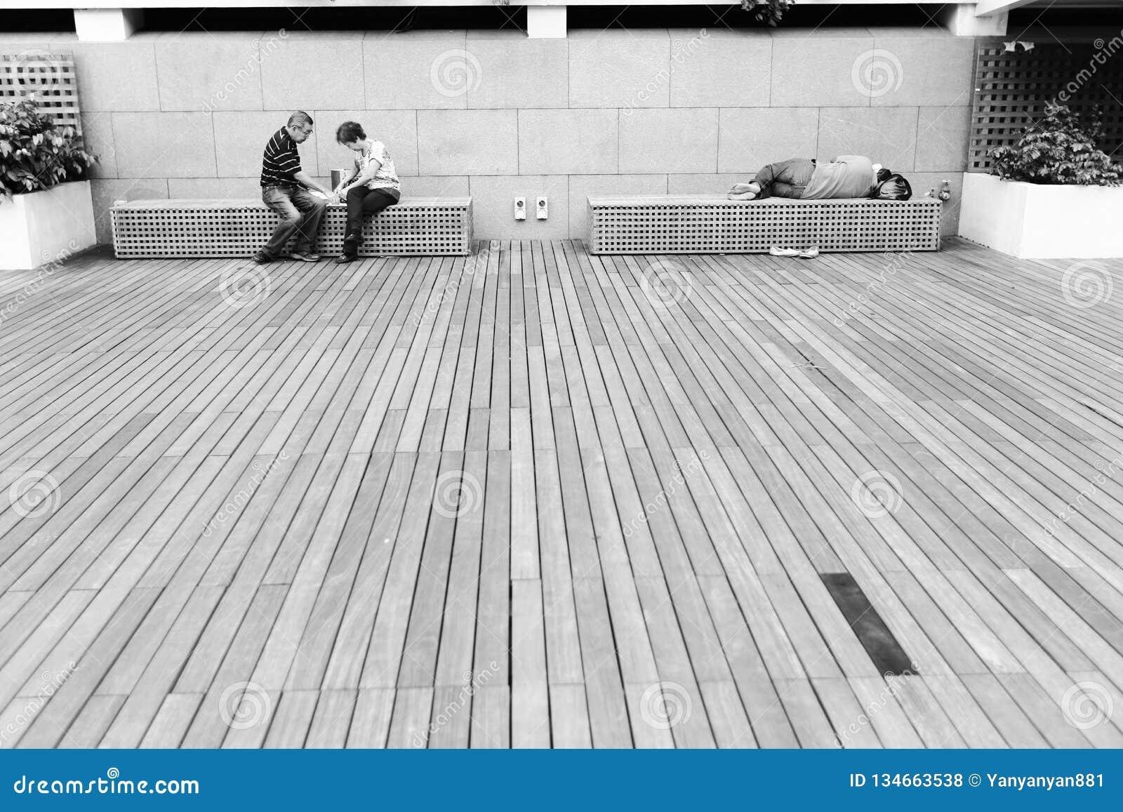 Dakloze mensenslaap op een bank bij het zand van de Jachthavenbaai, Singapore