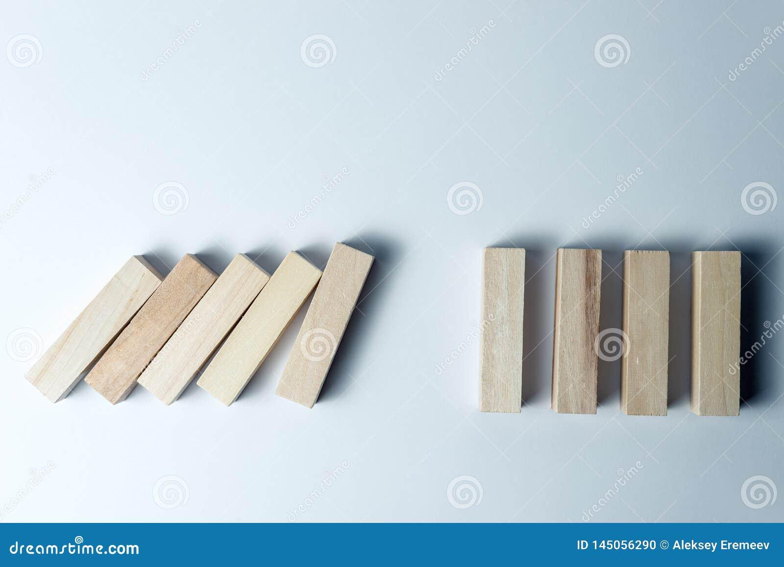 Dalende houten kubussen, als symbool van nederlaag, verkeerde besluit en instorting, betreffende een ongelijke witte achtergrond