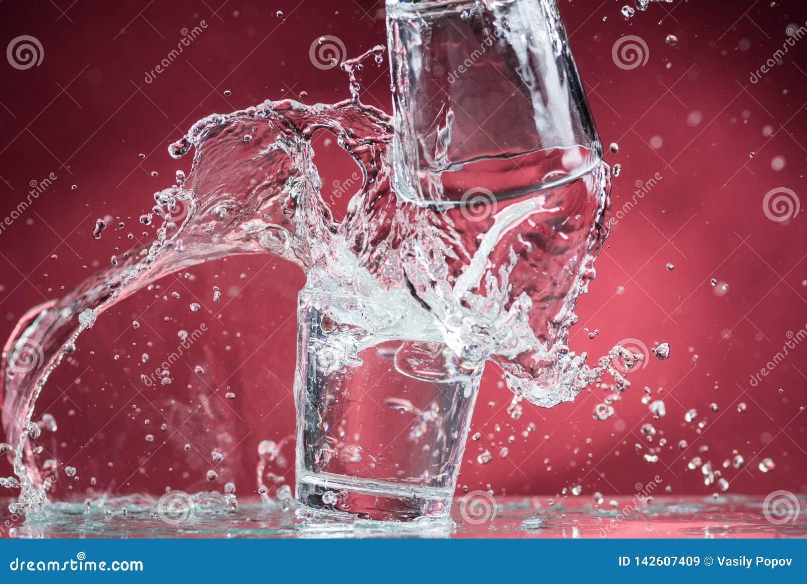 Dalende kleine glazen en het morsen van water op een blauwe achtergrond