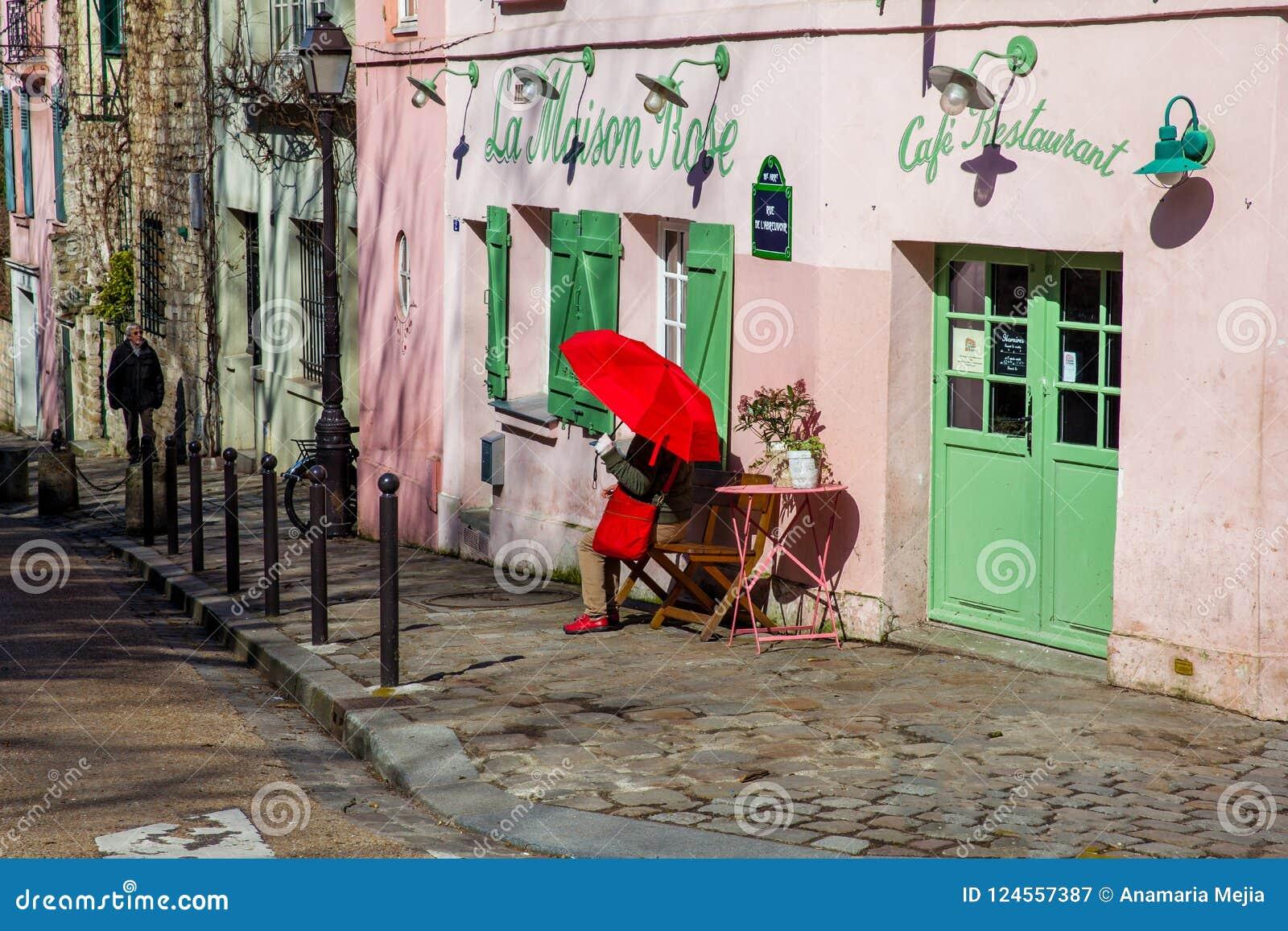 Dam med ett rött paraply på den rosa husrestaurangen i den berömda Montmartre