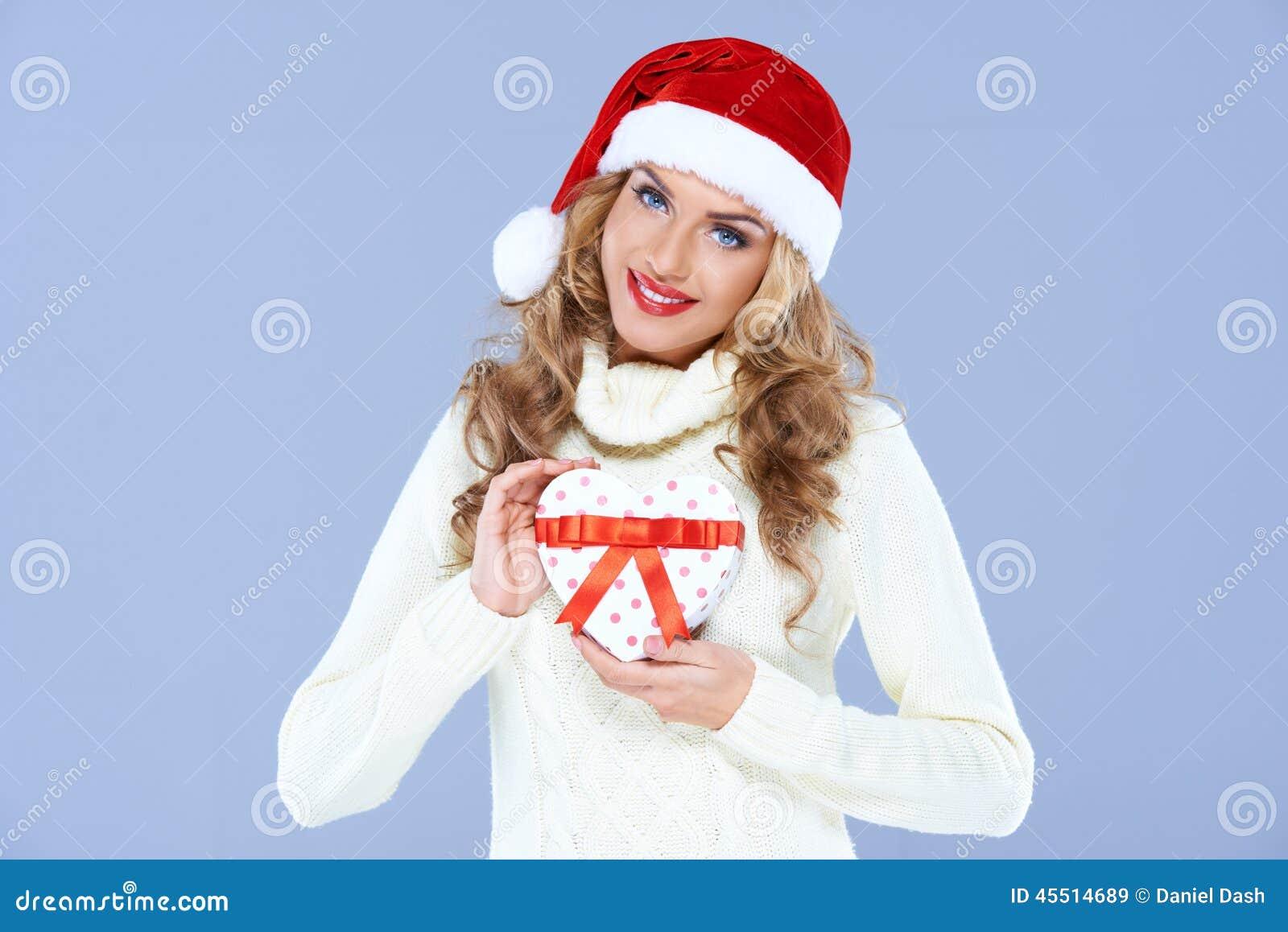 Dama jest ubranym Santa kapeluszowego przedstawia prezent