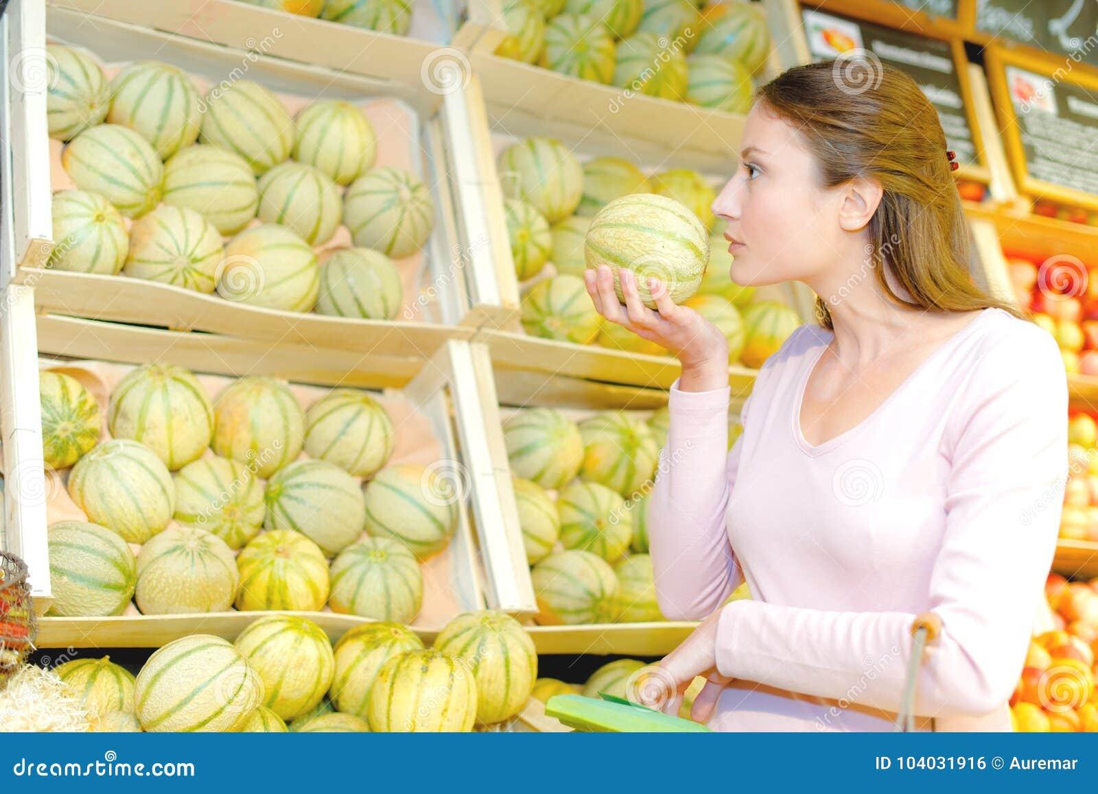 Dama wącha melon dla dojrzałości