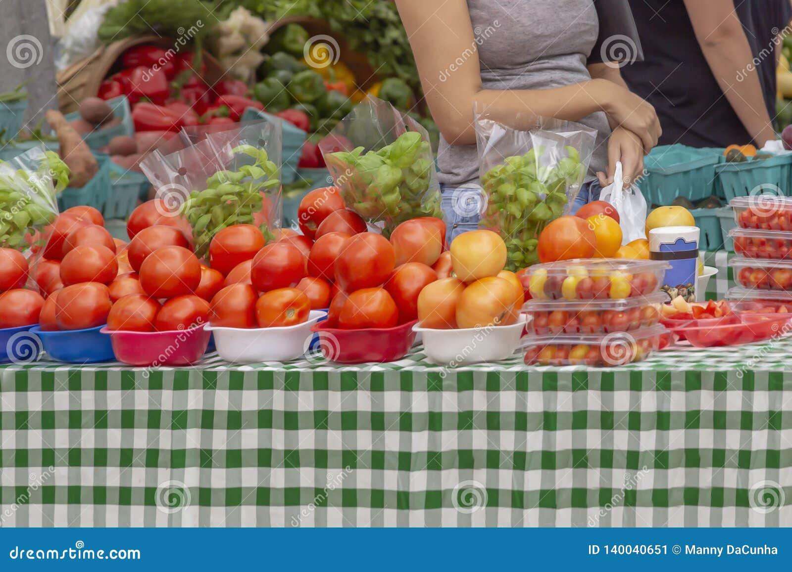 Dama zatrzymuje przy stołem wypełniającym z wibrującymi czerwonymi pomidorami przy plenerowym rynkiem