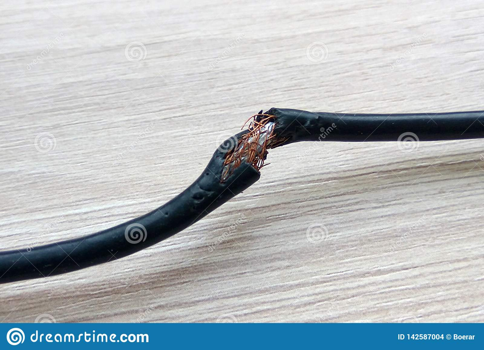Damaged black electric cord on wooden table or floor background. Dangerous broken electrical cable
