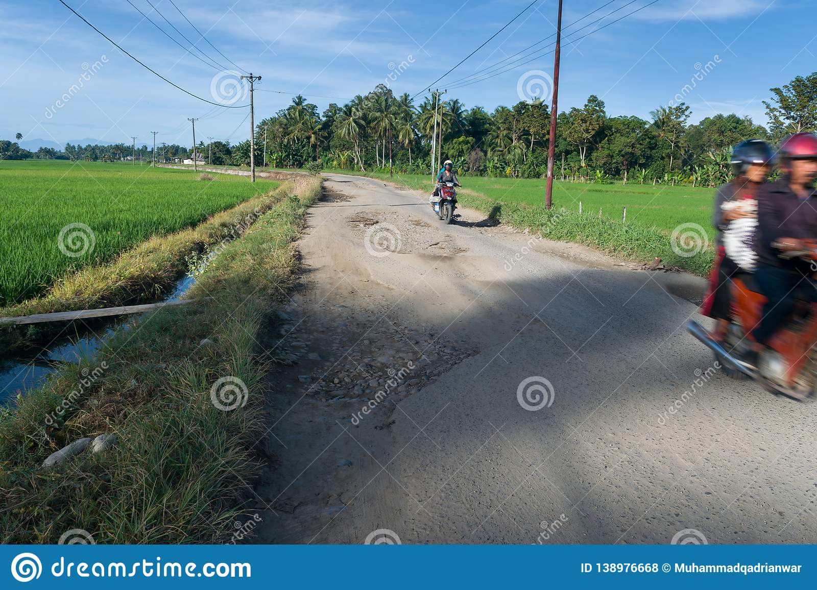 Damaged Road In Developing Country. Damaged road passed by several motorbike in developing country on a sunny morning with rice field on it`s both sides royalty free stock photos