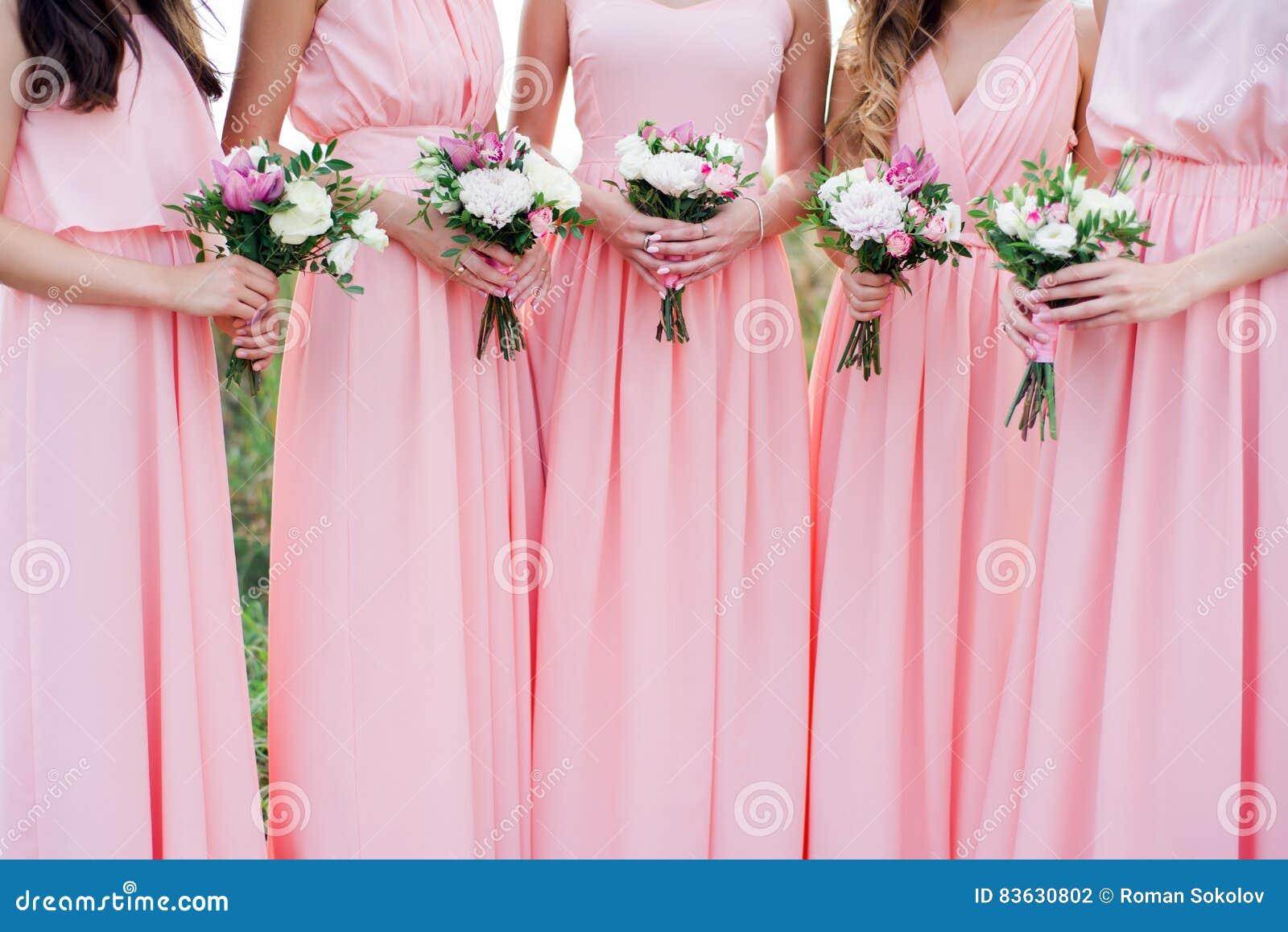 Damas De Honor Gloriosas En Los Vestidos Rosados Que Sostienen Las ...