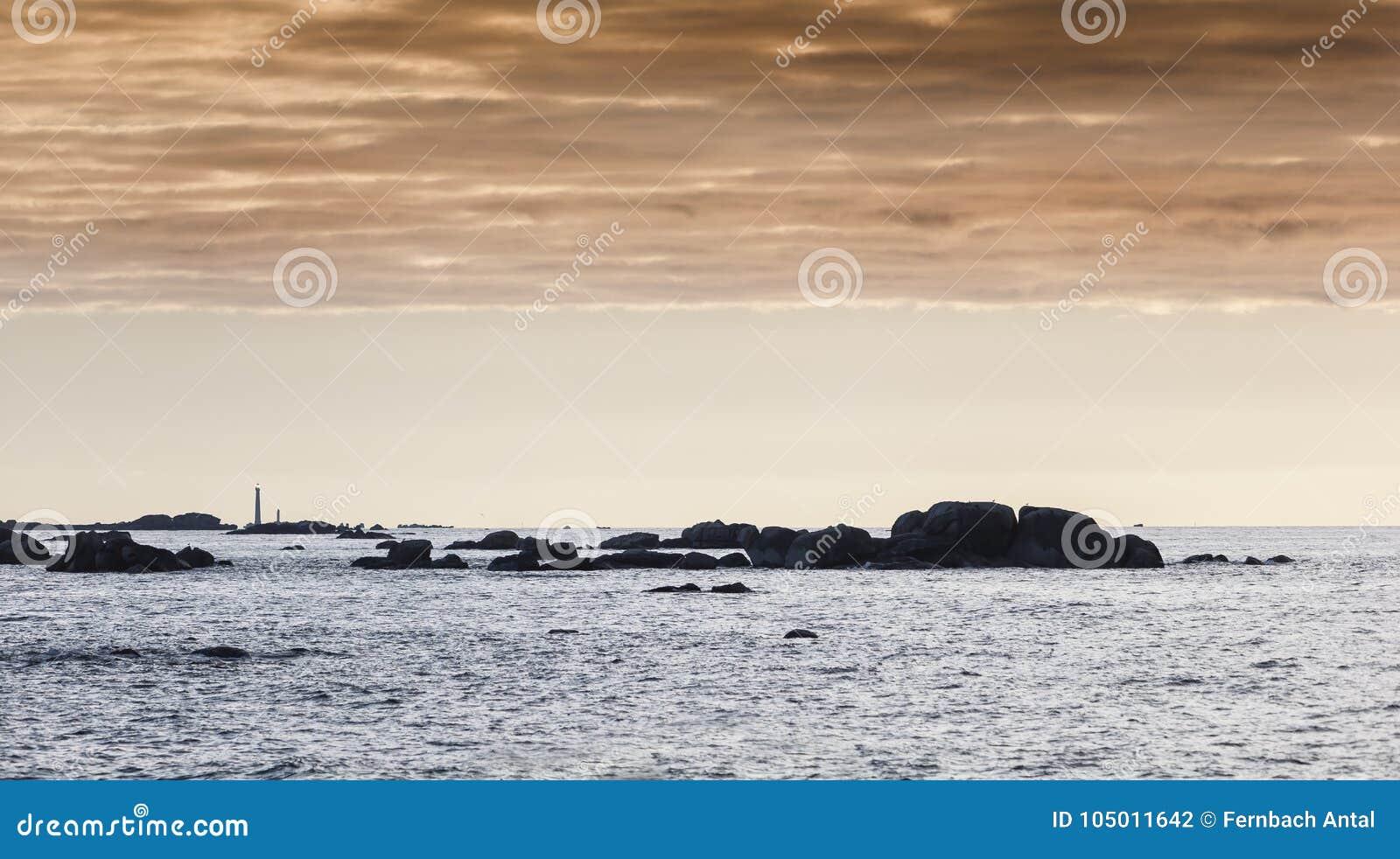 Damatic tänder kustlinjen i Brittany, Frankrike i solnedgång med en li