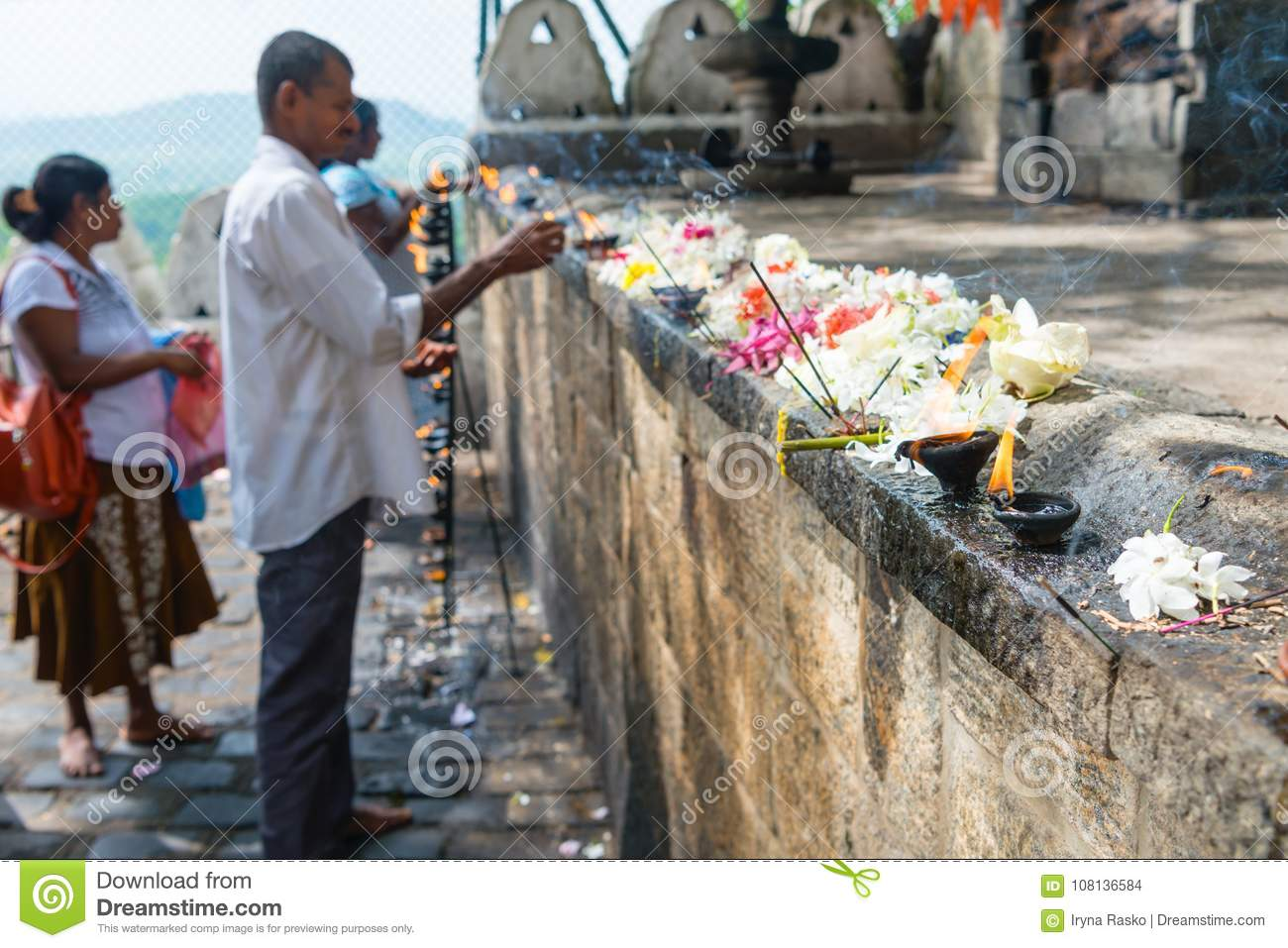 People place offerings with fragrant sticks, fresh flowers and b