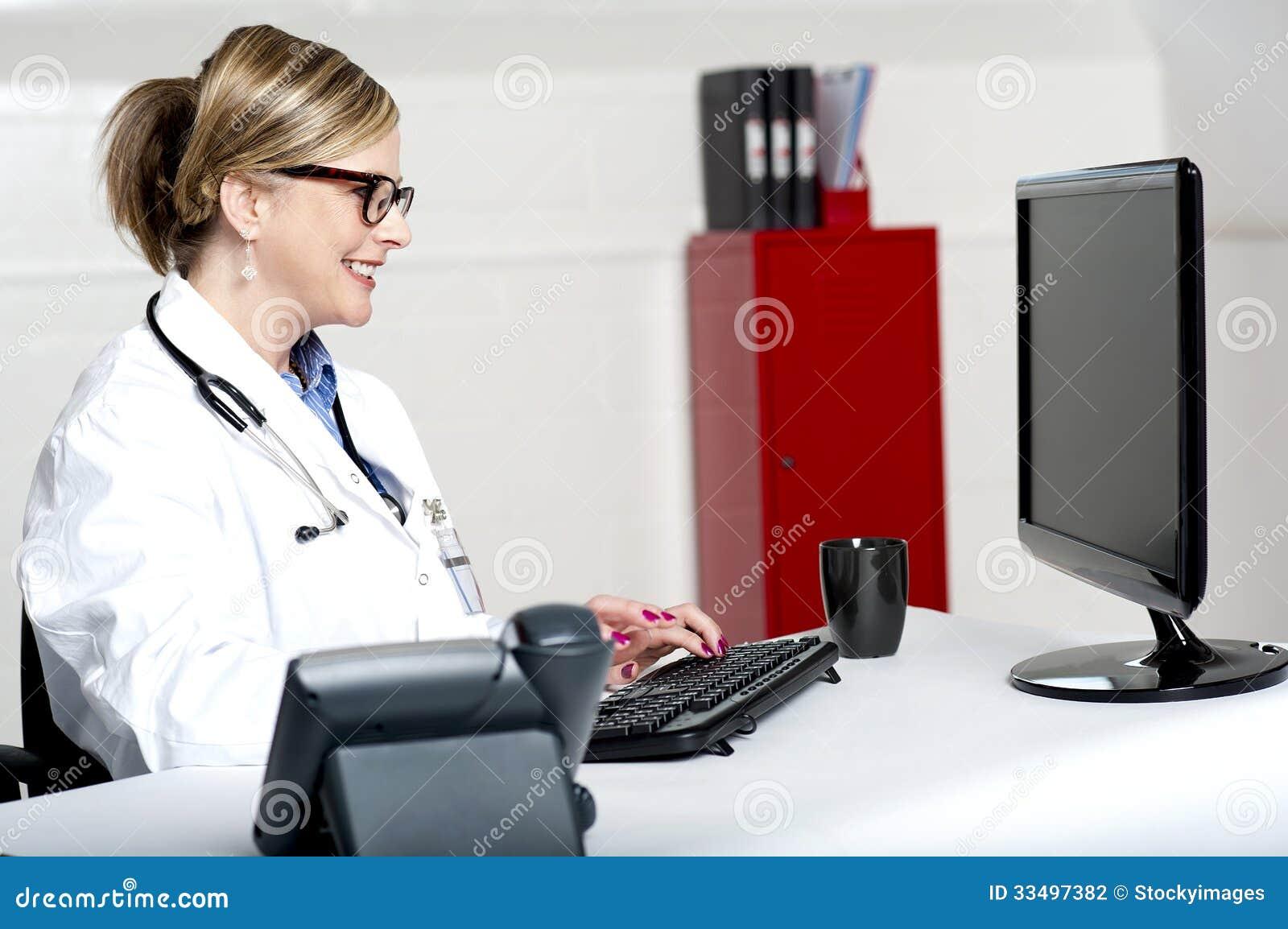Damdoktor som arbetar på datoren
