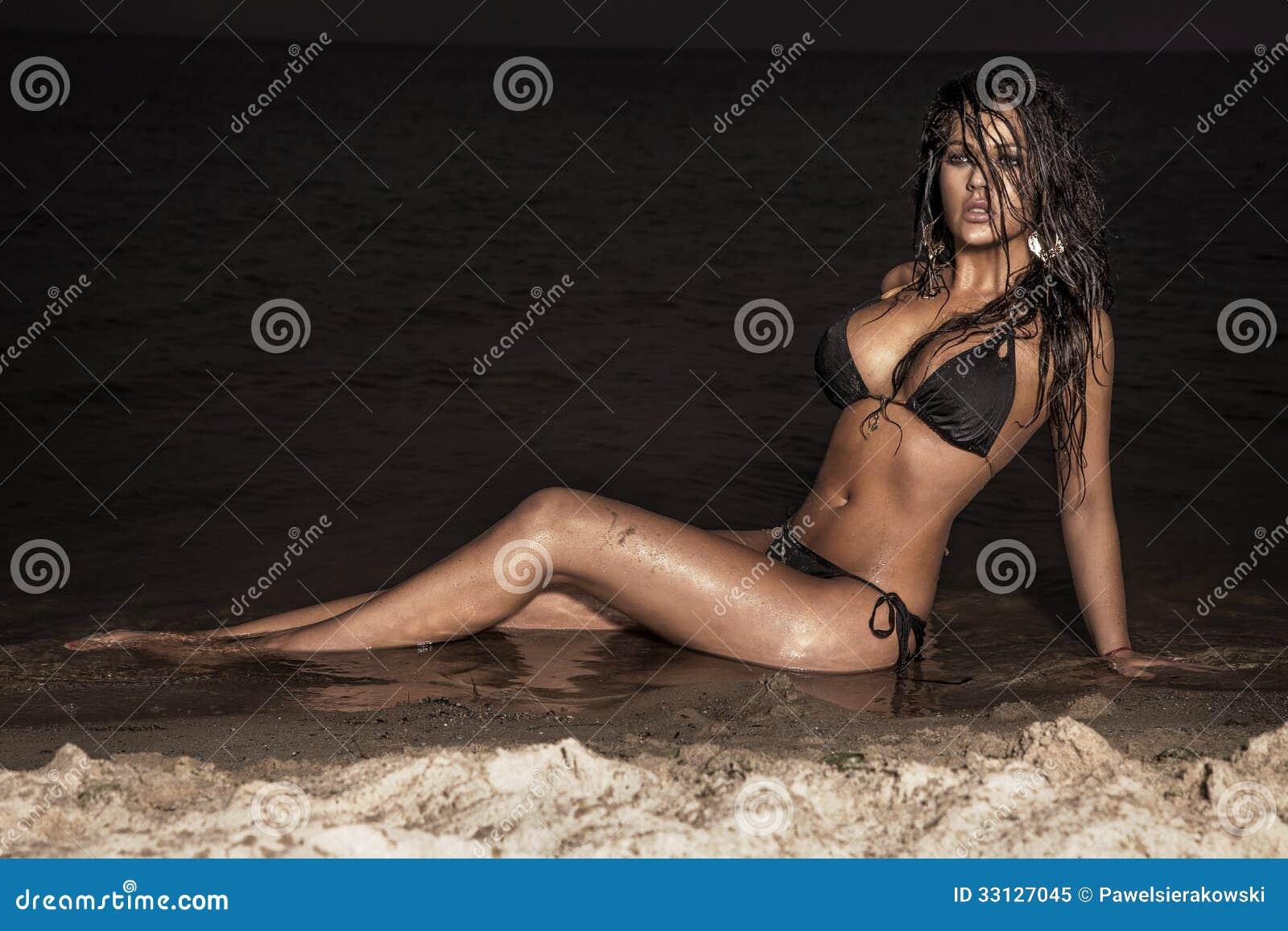Dame attirante de brune posant sur la plage la nuit.