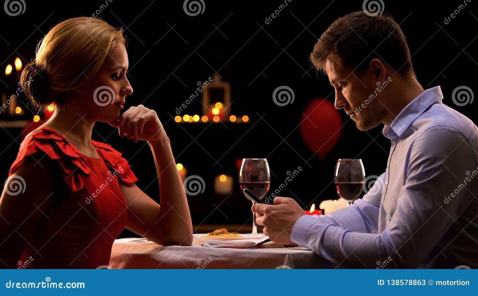 Dame bouleversée regardant le smartphone de défilement d ami, mauvaise date, dépendance d instrument
