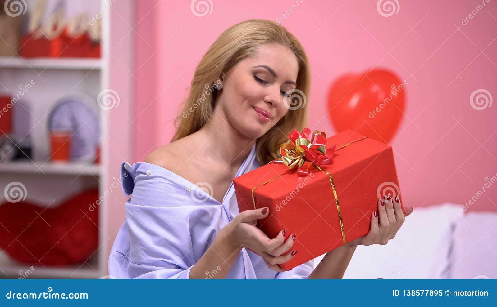 Dame de sourire attirante jugeant le boîte-cadeau ravi avec surprise, Saint Valentin