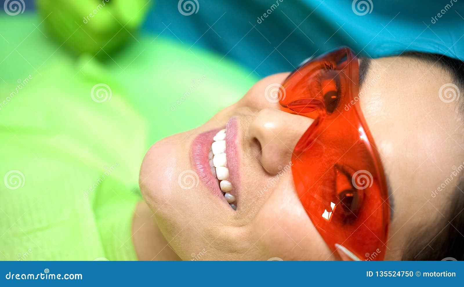 Dame de sourire satisfaite de la professionnalisme de dentiste, art dentaire pour la dent ébréchée