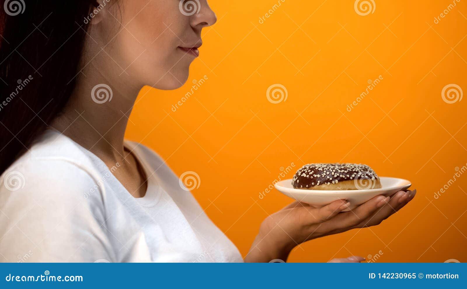 Dame die chocoladedoughnut bekijken, hoog-calorie zoet voedsel, verhoogde glucose